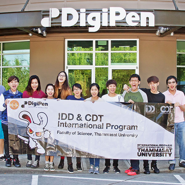 Students from Thammasat University in Thailand pose with a banner in front of DigiPen's main entrance