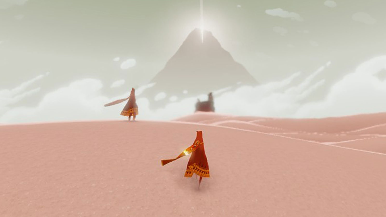 Screenshot from Playstation 3 game Journey, featuring characters walking on pink sand toward a mountain