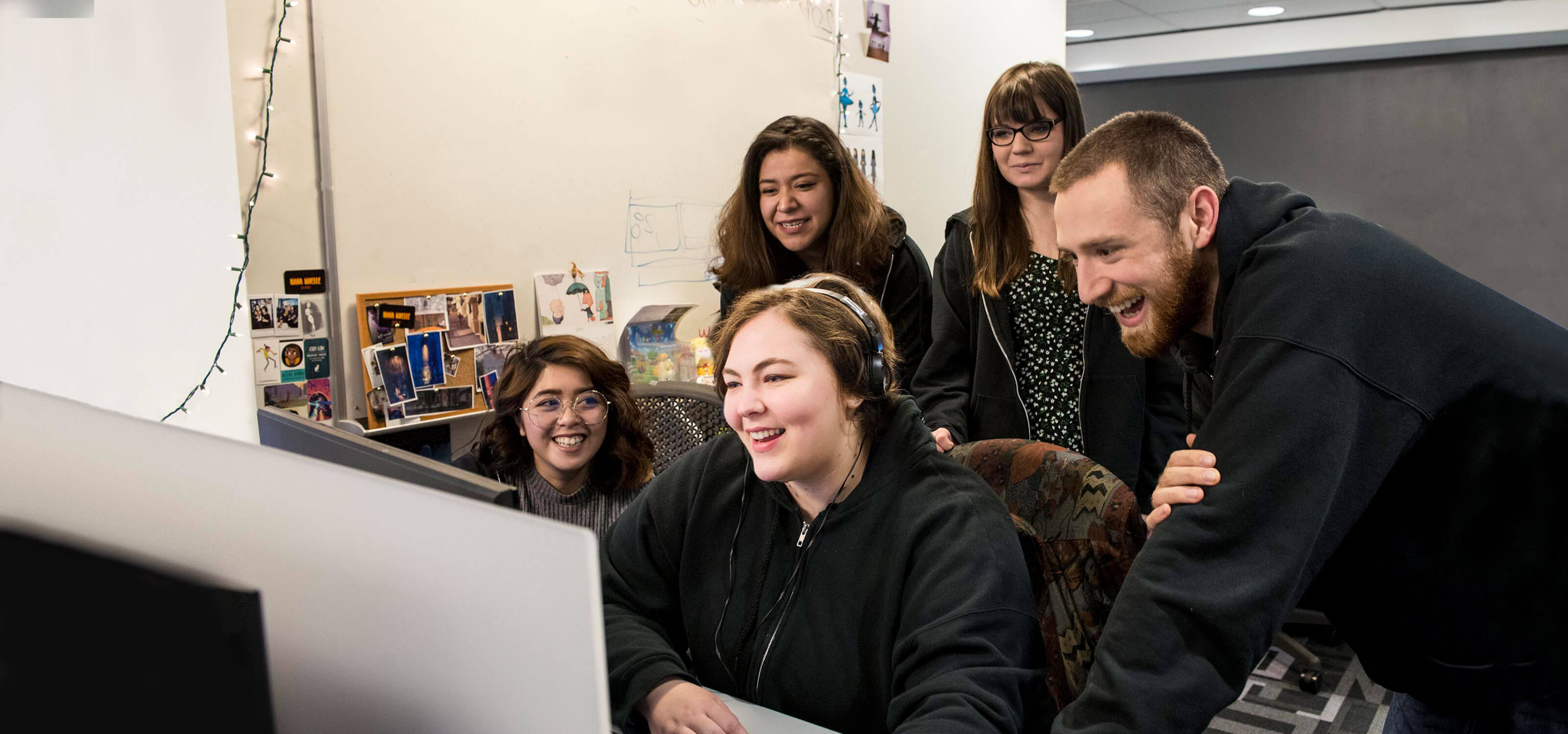 A group of smiling people stand behind a woman sitting at a computer monitor, looking over her shoulder.