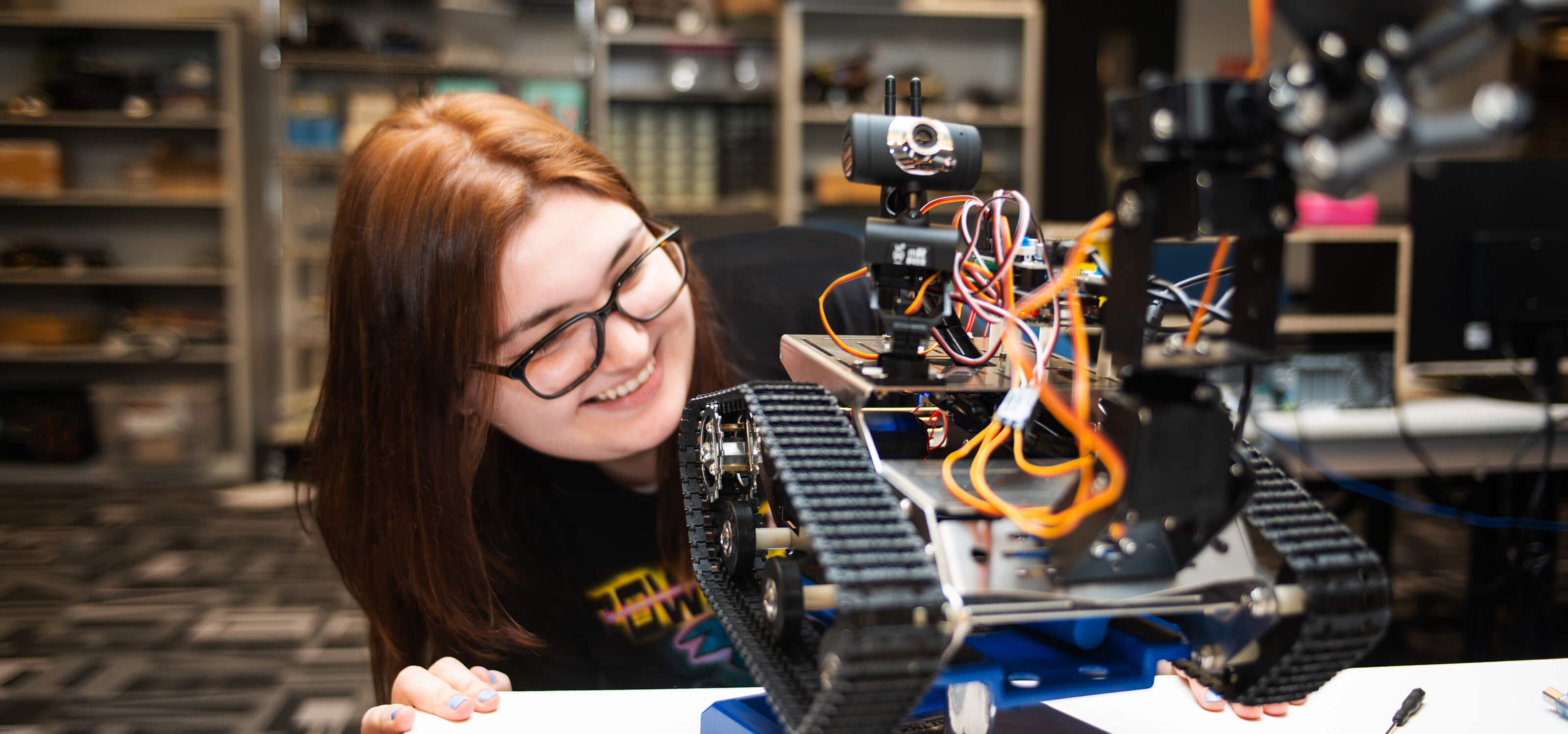 A DigiPen student smiles as she examines her robot