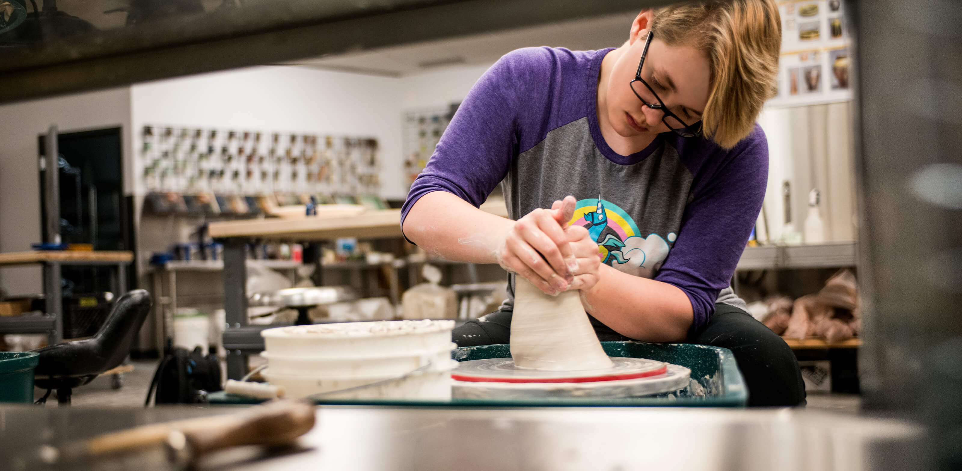 A student concentrates as she molds clay on a spinning wheel