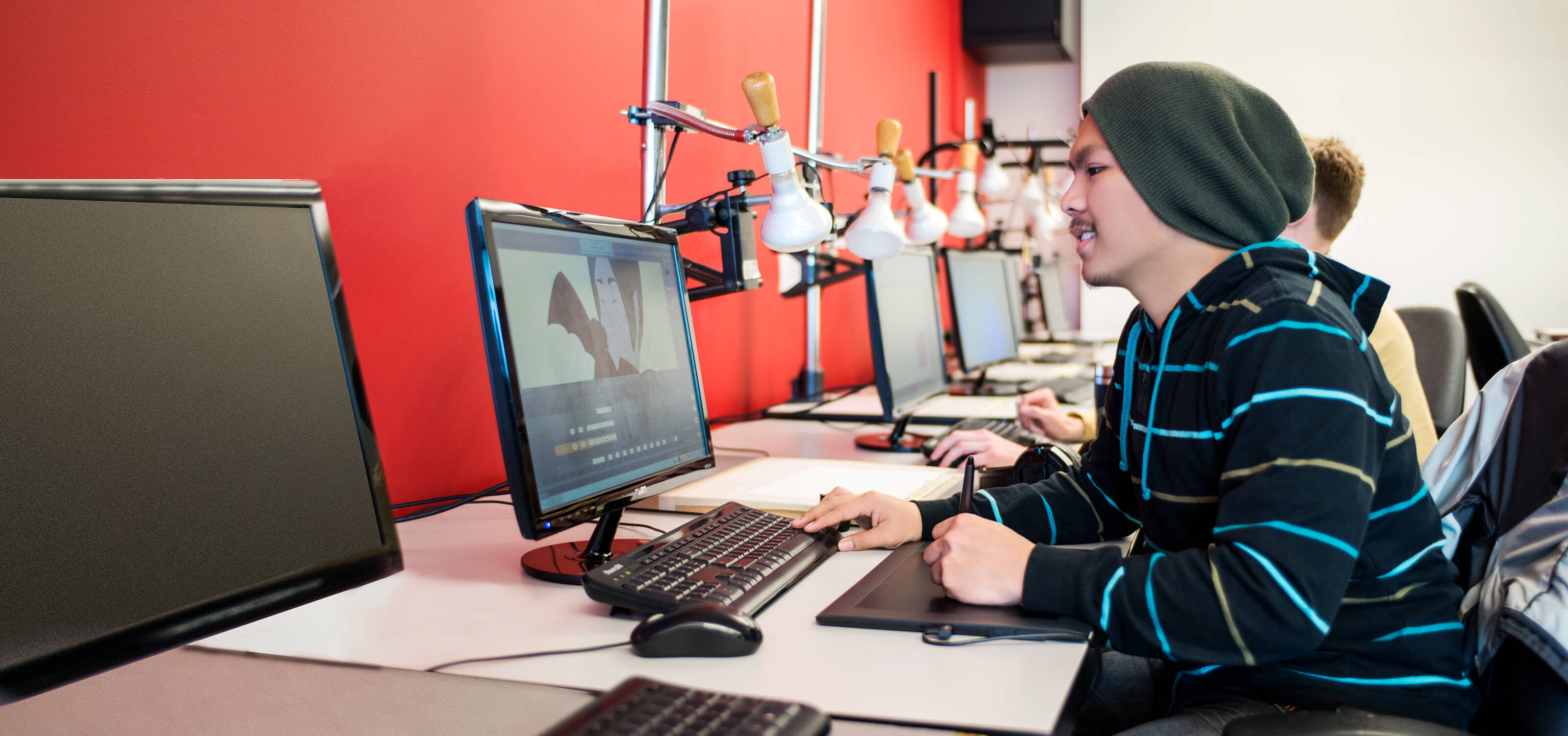 A DigiPen student smiling as he works on a computer animation