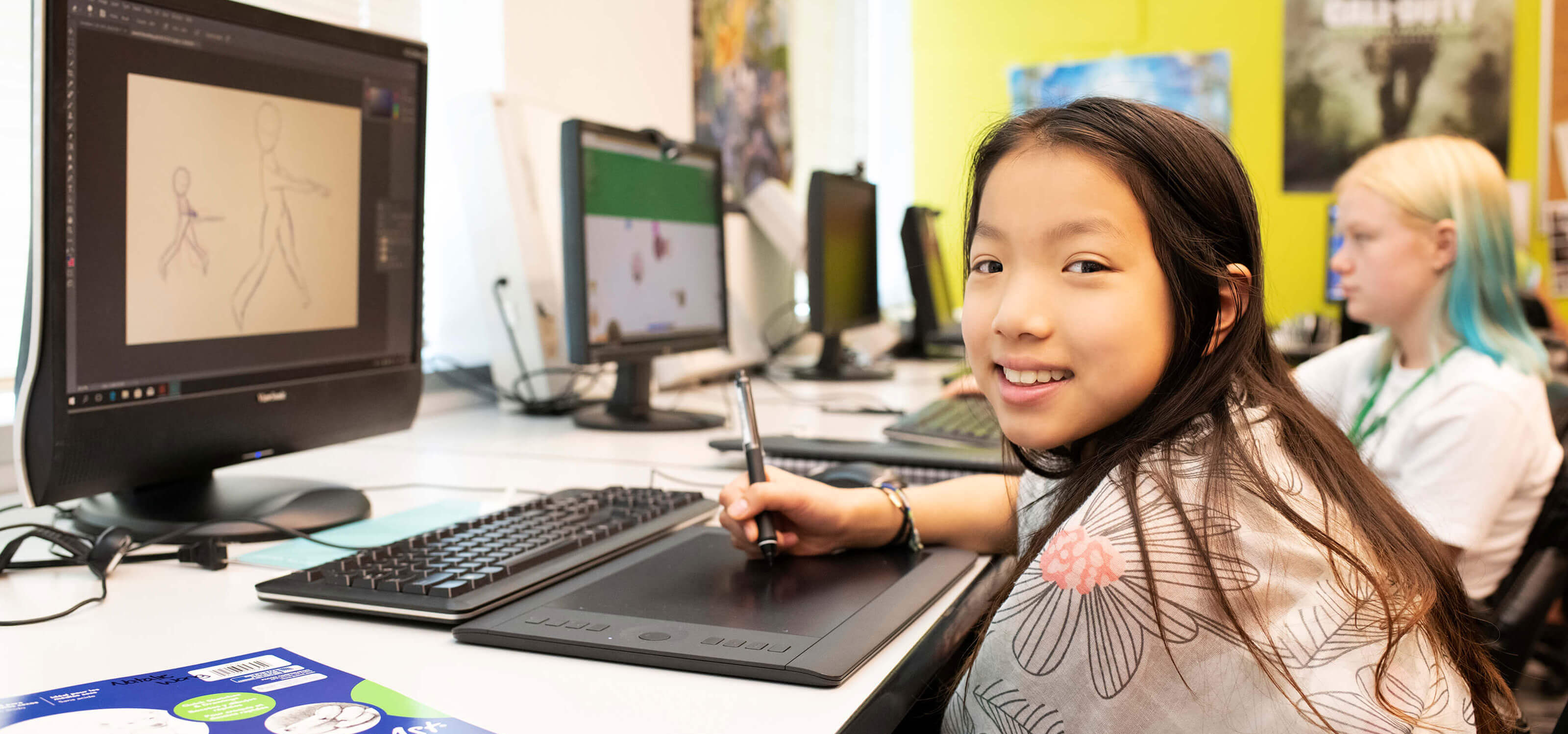 A young DigiPen Academy student smiling as she sits at a computer in a classroom at the DigiPen campus