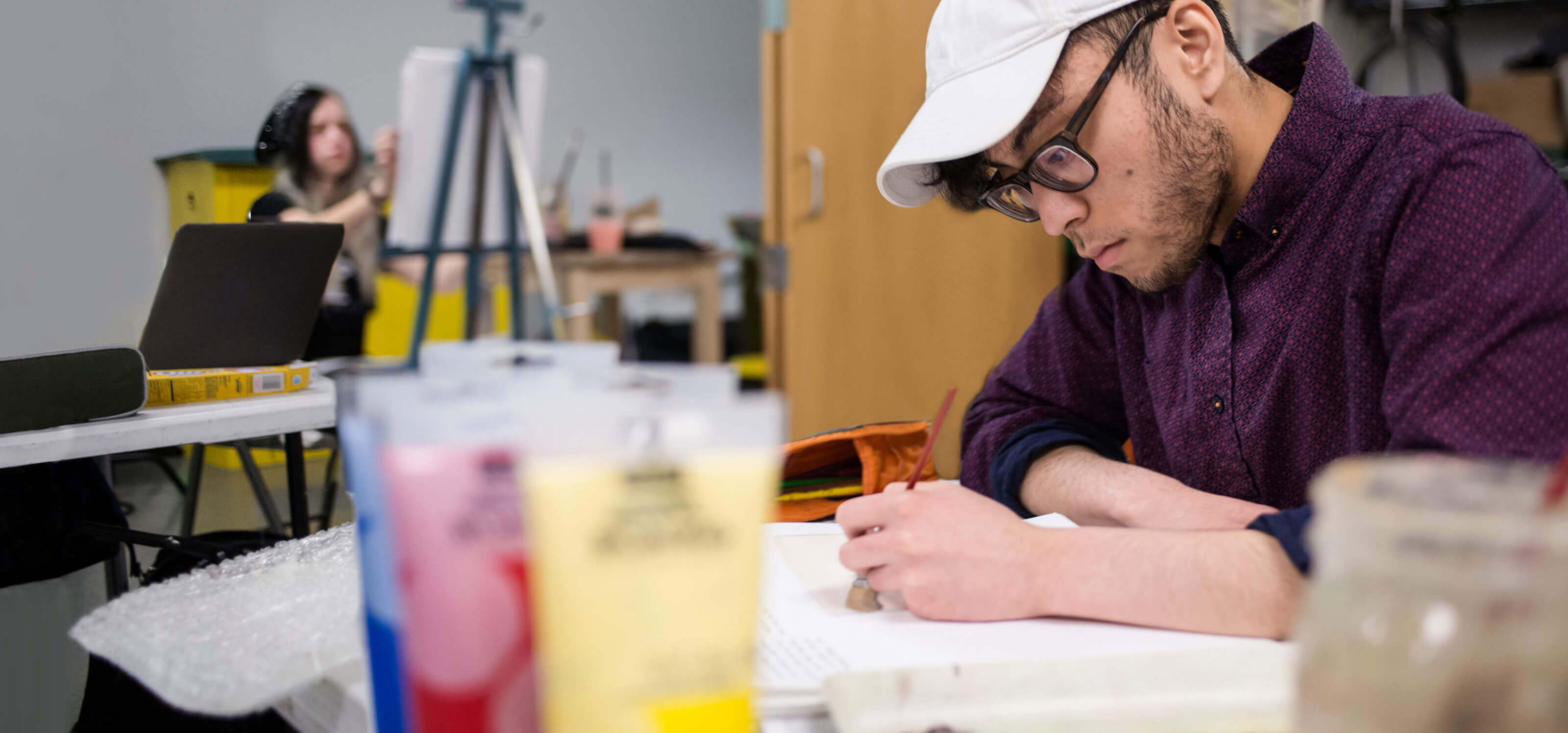 A man looks intently at the paint he is applying to a piece of paper. A woman in the background is painting with an easel.