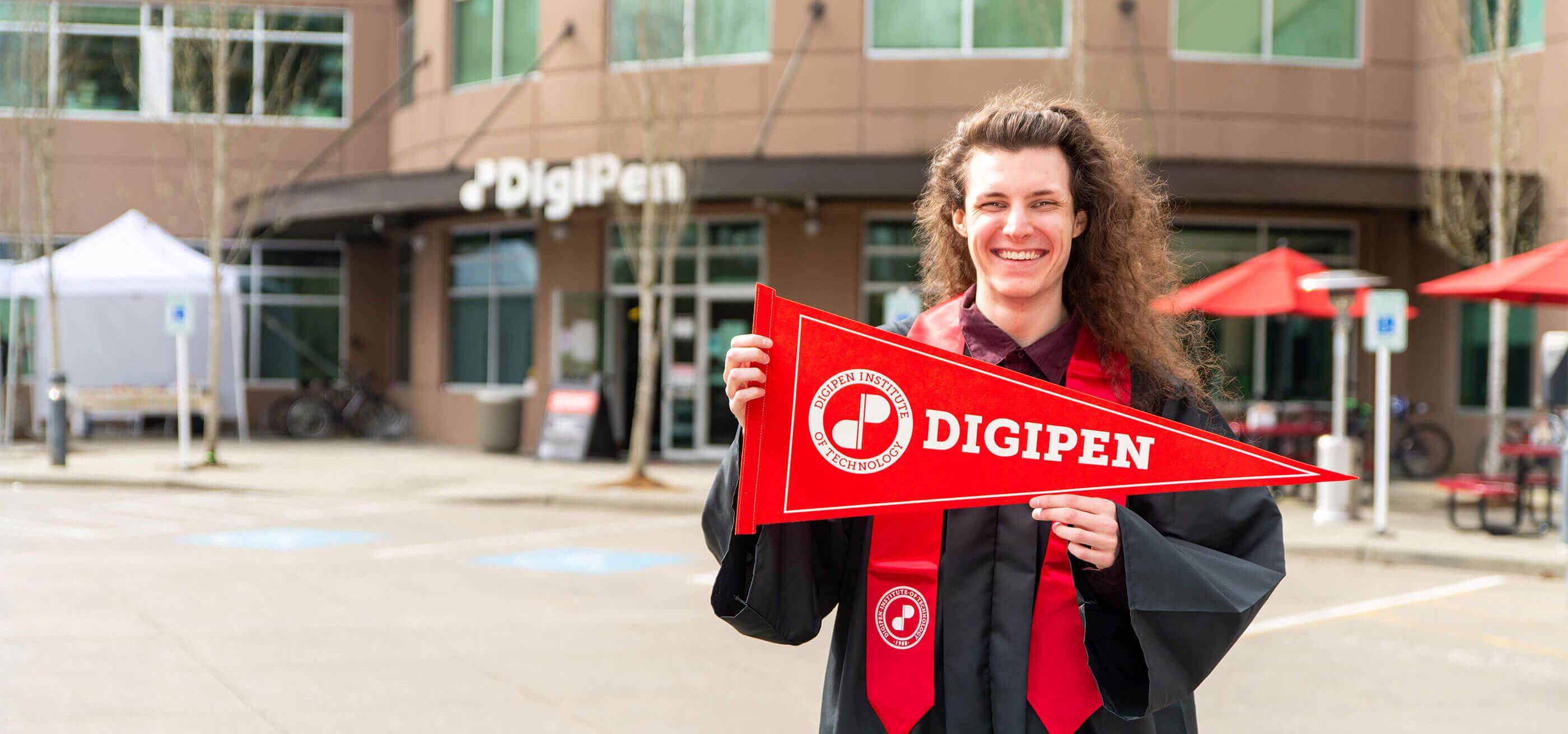 DigiPen graduate Felix Knight DigiPen holding pennant