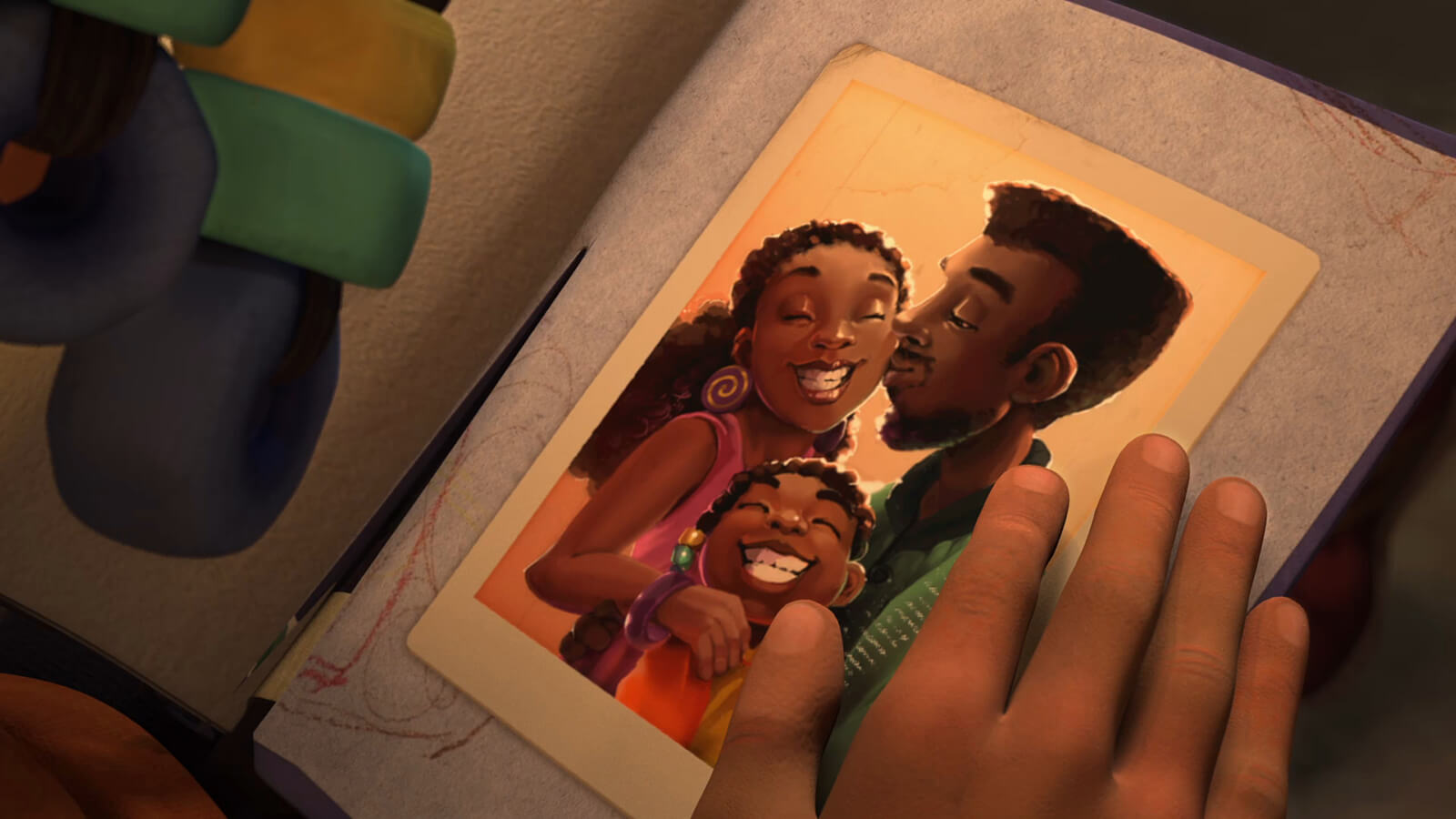 A hand is on a scrapbook containing a photo of a family, with a man kissing a smiling woman and a smiling girl below them