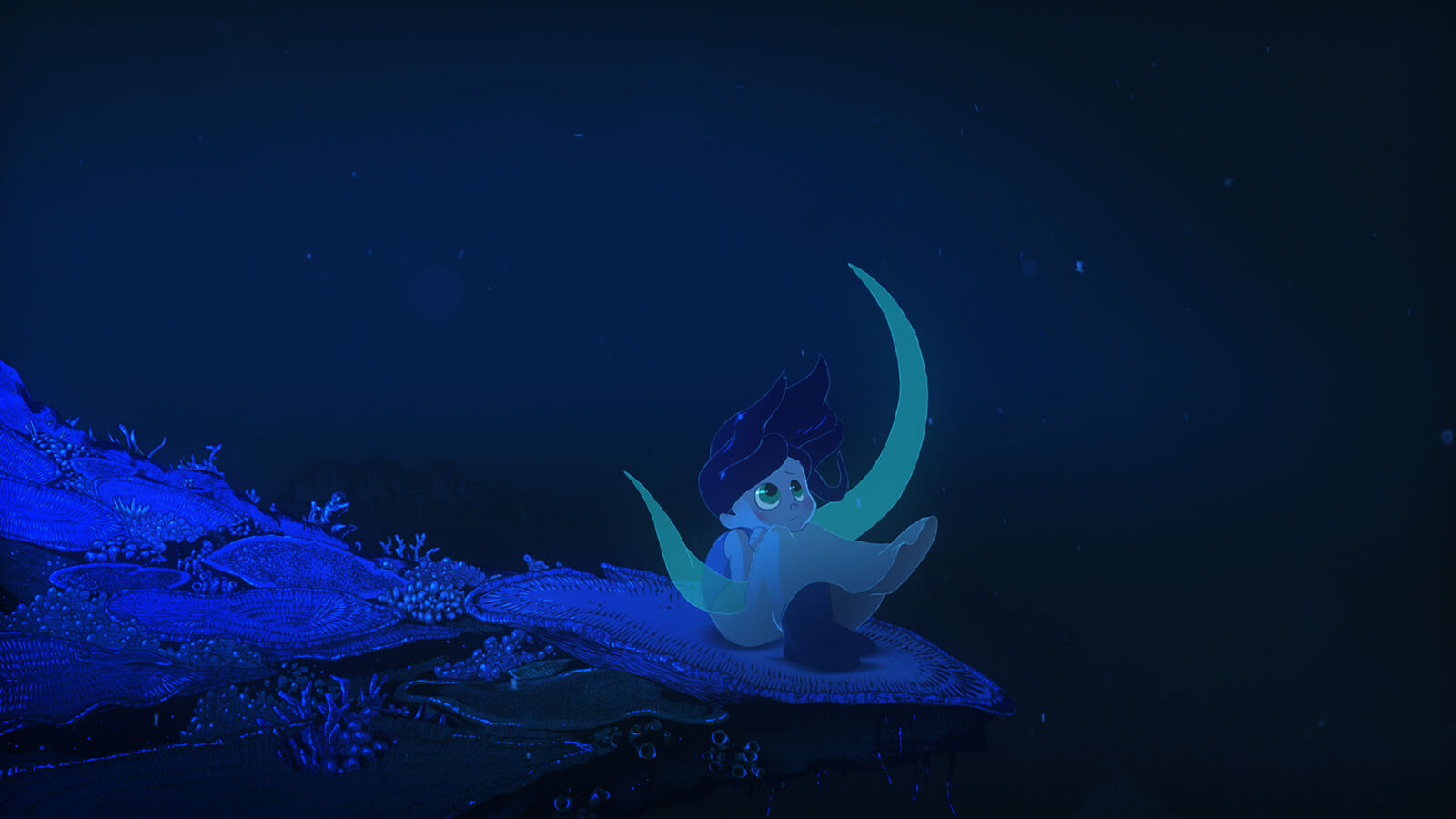 A girl sits on top of a flat coral seat underwater. She looks up into the dark sea.