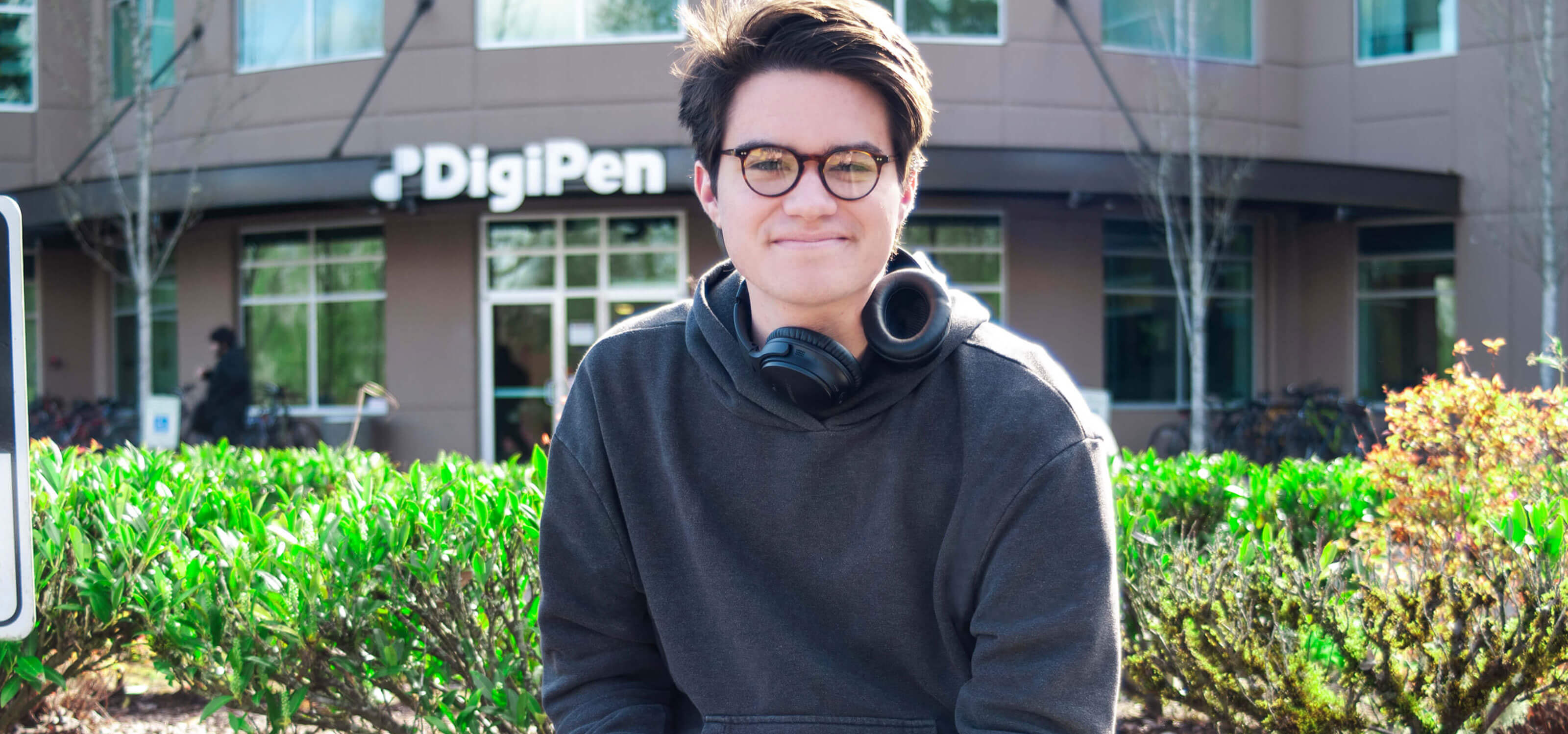 A student wearing headphones smiles on a sunny day in front of the DigiPen building