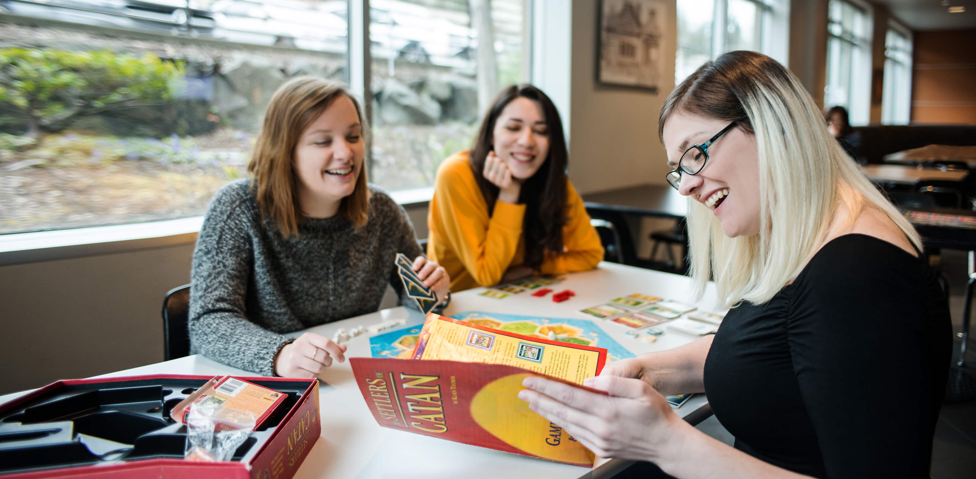 Students laughing as they play a board game in the DigiPen Cafe