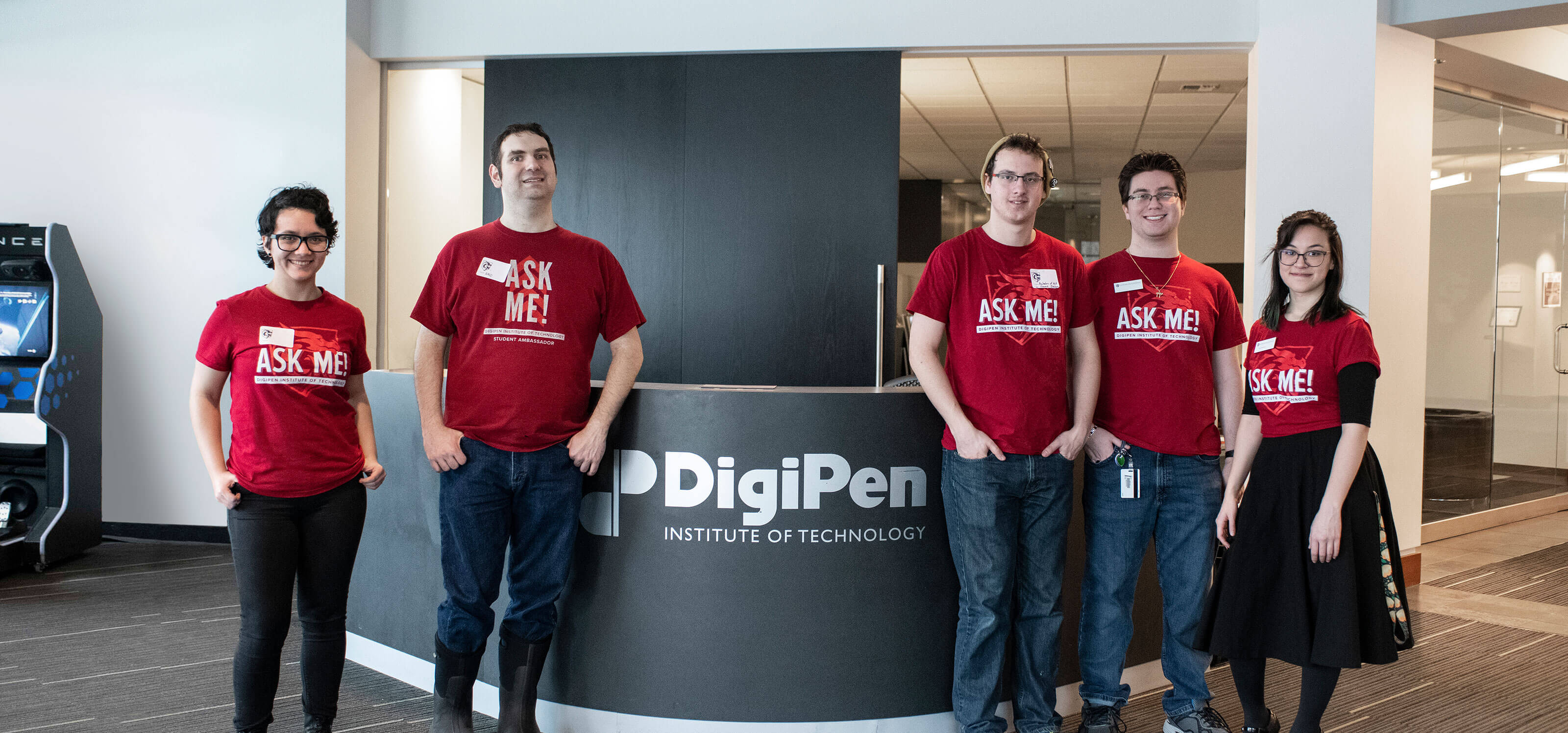 Five people in red t-shirts stand in front of a black desk with DigiPen Institute of Technology written in white letters.