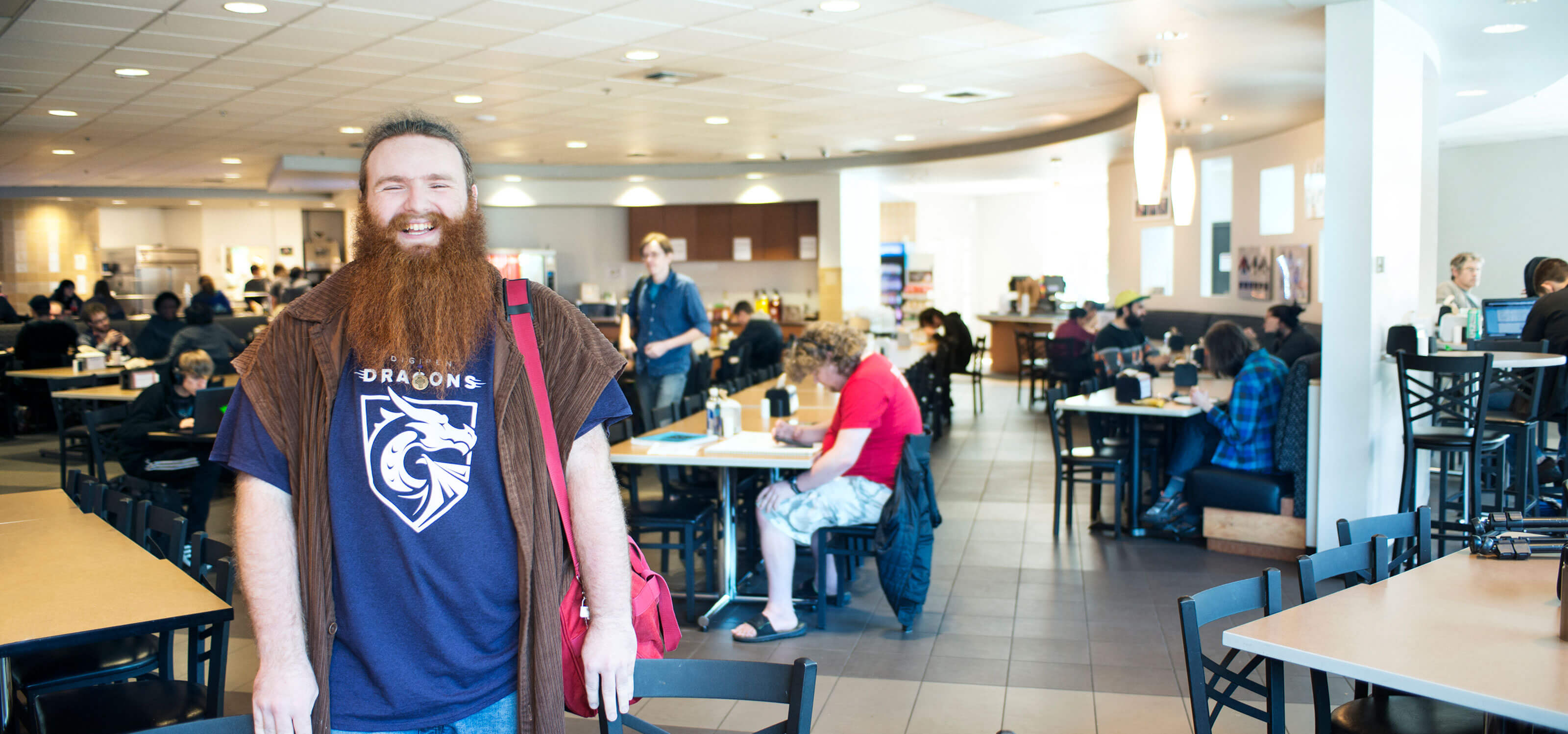 A smiling, bearded man wearing a purple, dragon-logo t-shirt stands in a dining hall where others are seated at tables.