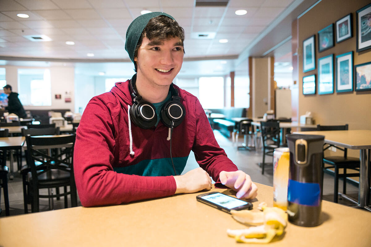 A smiling man in a maroon parka with headphones draped over his neck sits at a table in a brightly lit dining hall.