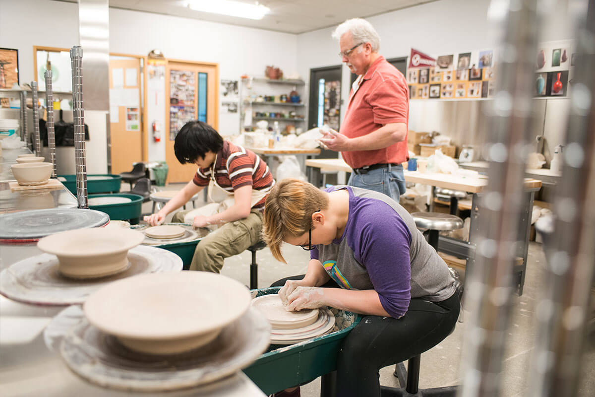Students work intently at pottery wheels in a ceramics studio as an instructor behind them looks over their shoulders.