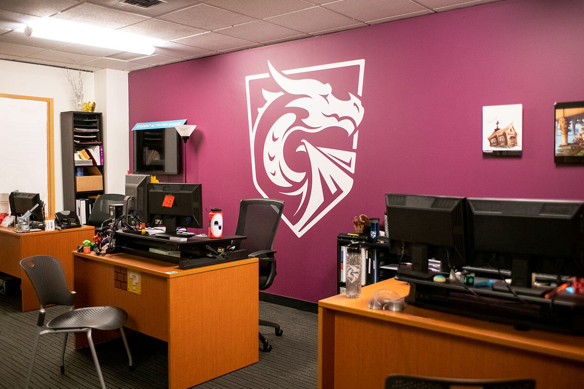 An office space with desks and computers in front of a maroon-colored wall with a large white logo of a dragon painted on it.