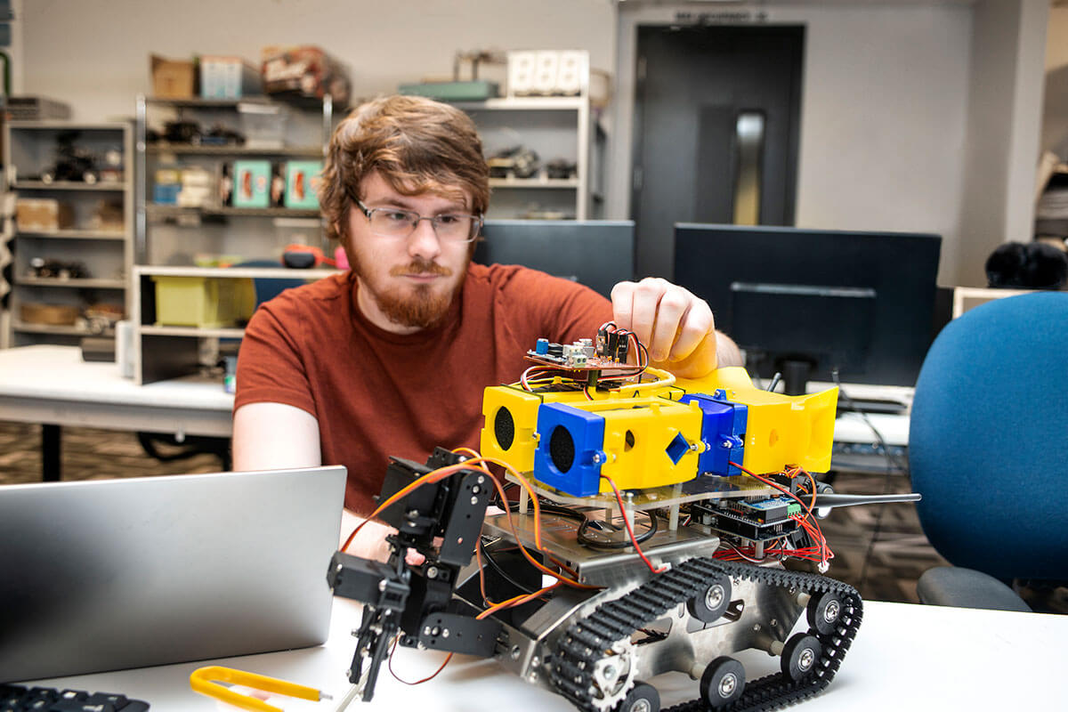A man in an orange t-shirt sits working on a blue-and-yellow robot with exposed circuits, plastic, metal, and treads.