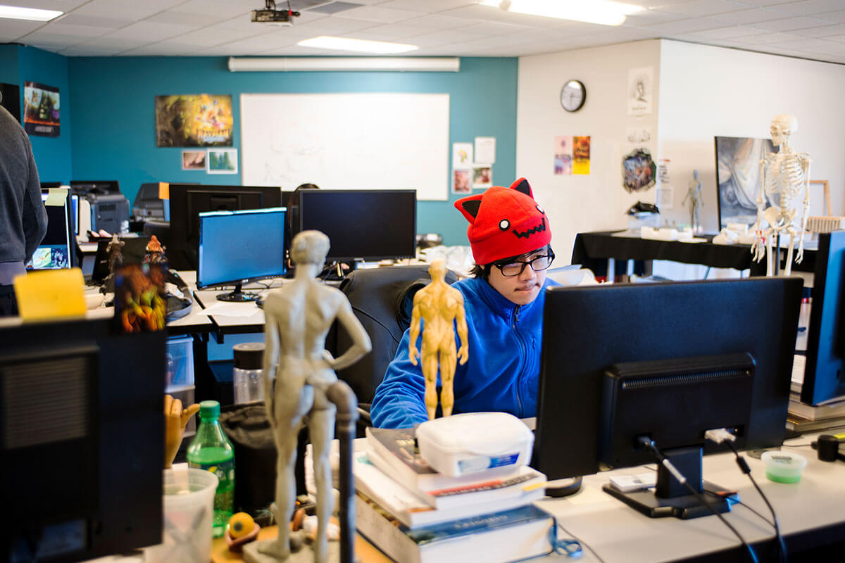 A man in a blue parka and red beanie sits at a computer in a room filled with anatomical models, both miniature and life-size