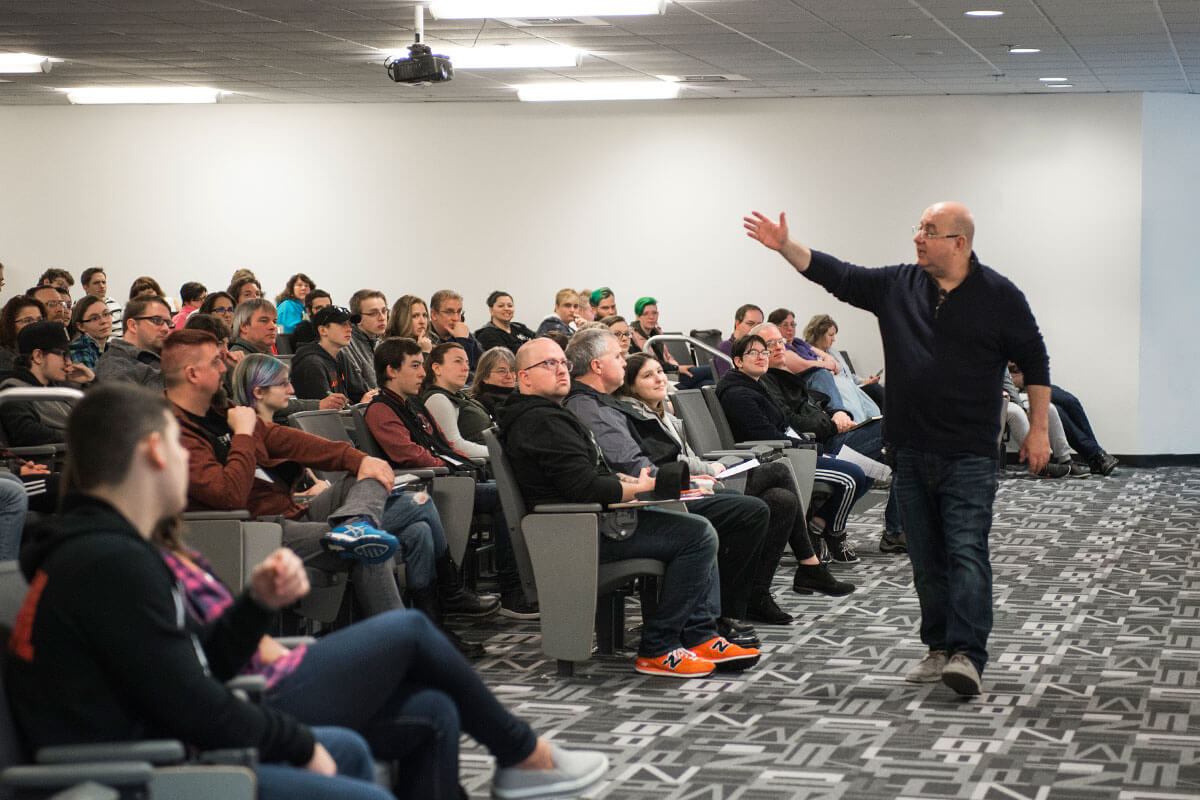 A man in jeans and a black parka animatedly addresses a group of people in a large auditorium-style classroom.