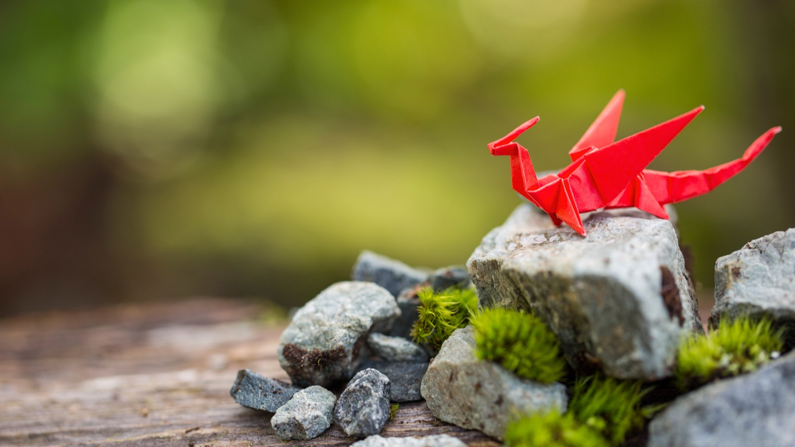 A dragon crafted from red origami paper sitting on a mossy rock