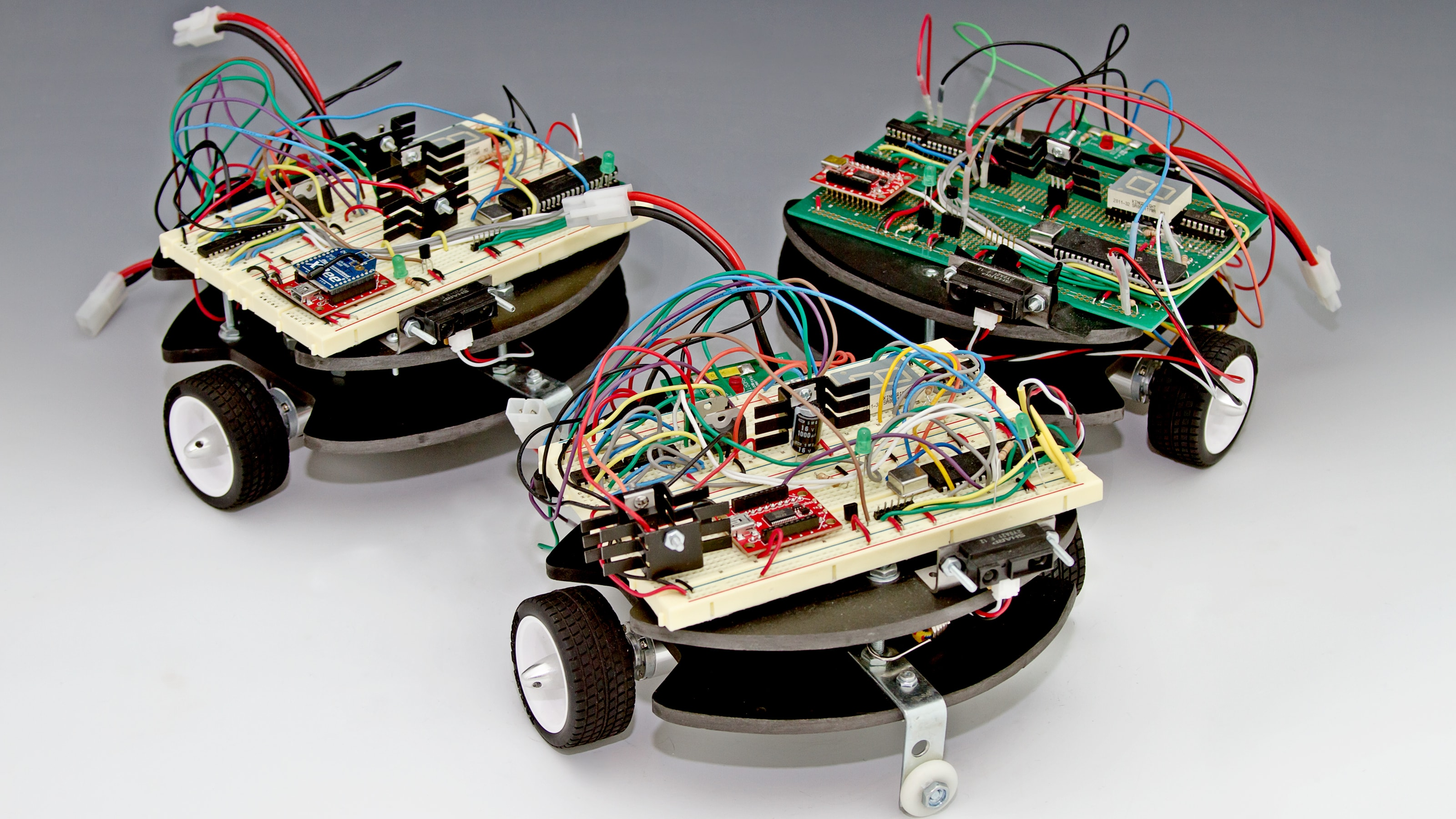 Three square robots with rounded fronts, black and white wheels and exposed circuitry.