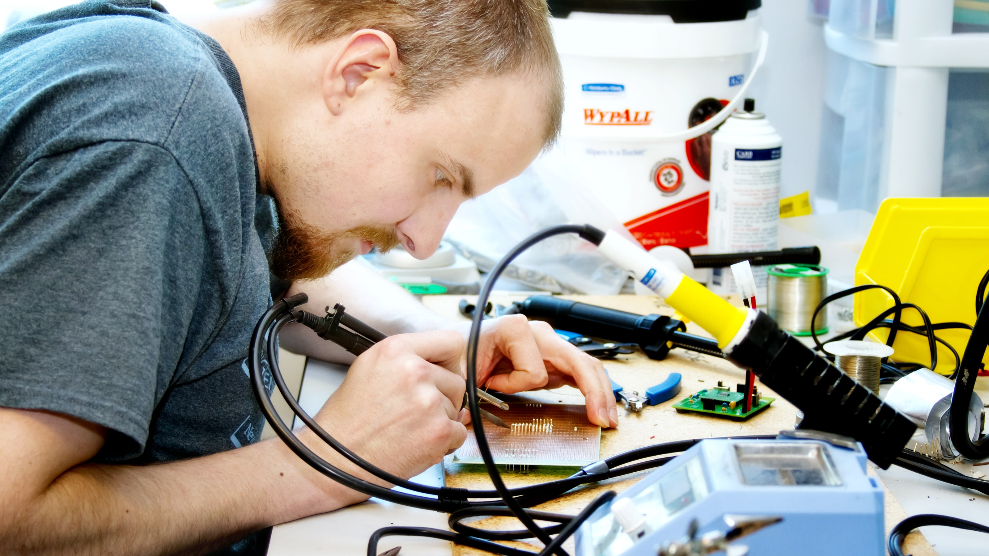 A student solders a circuit board on a desk cluttered with tools.