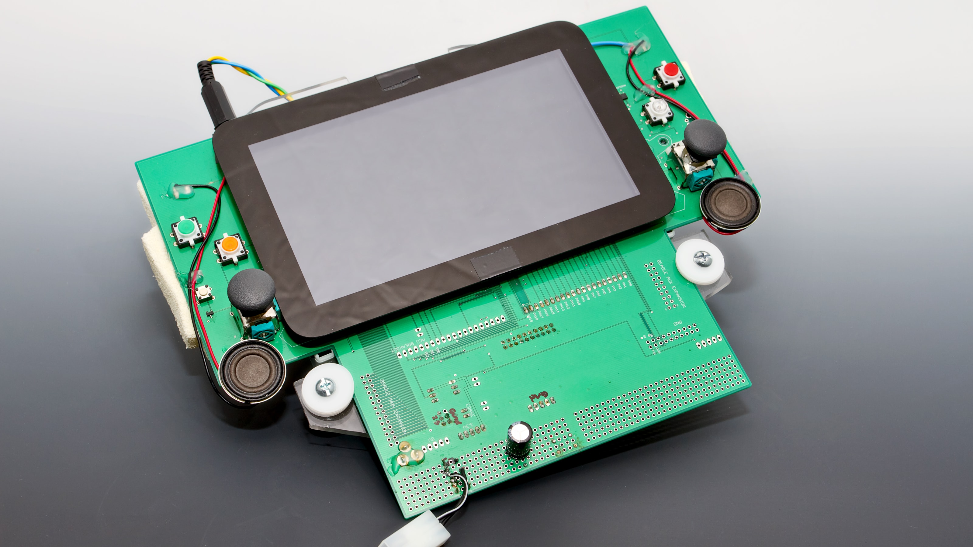 A screen mounted to a green circuit board with two control sticks.