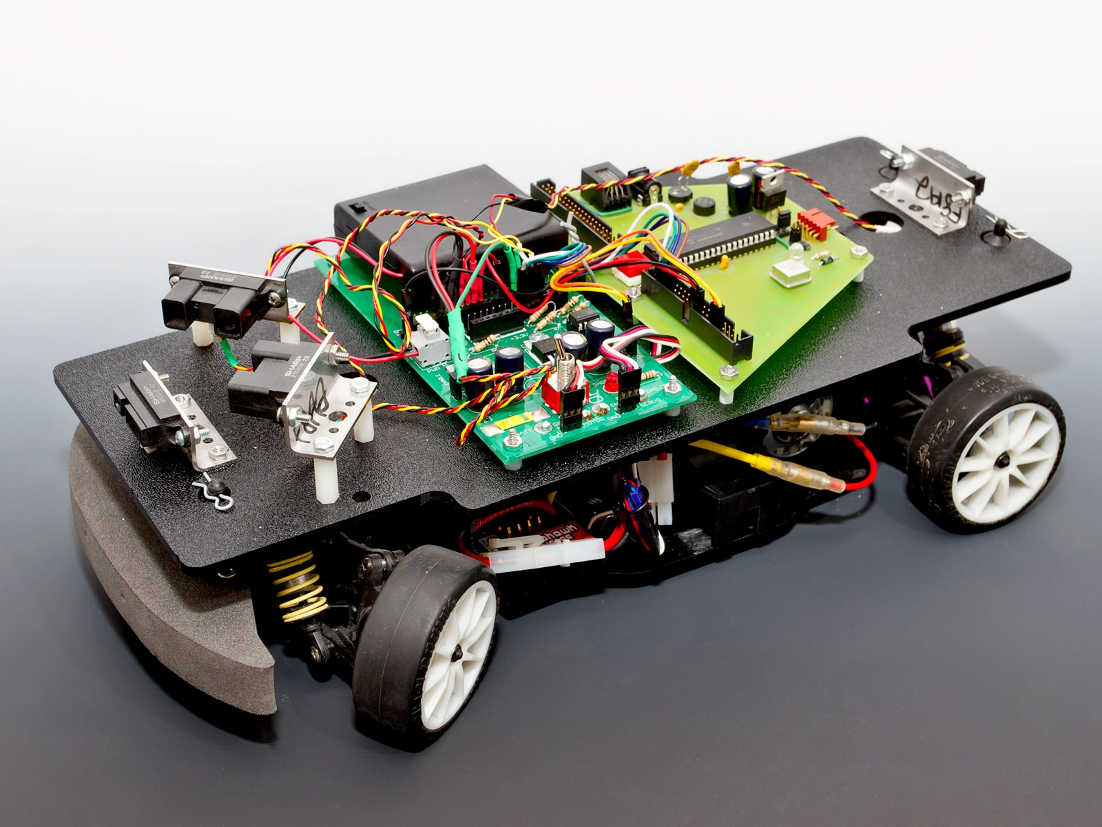 A four wheeled car with infrared sensors and exposed circuitry.