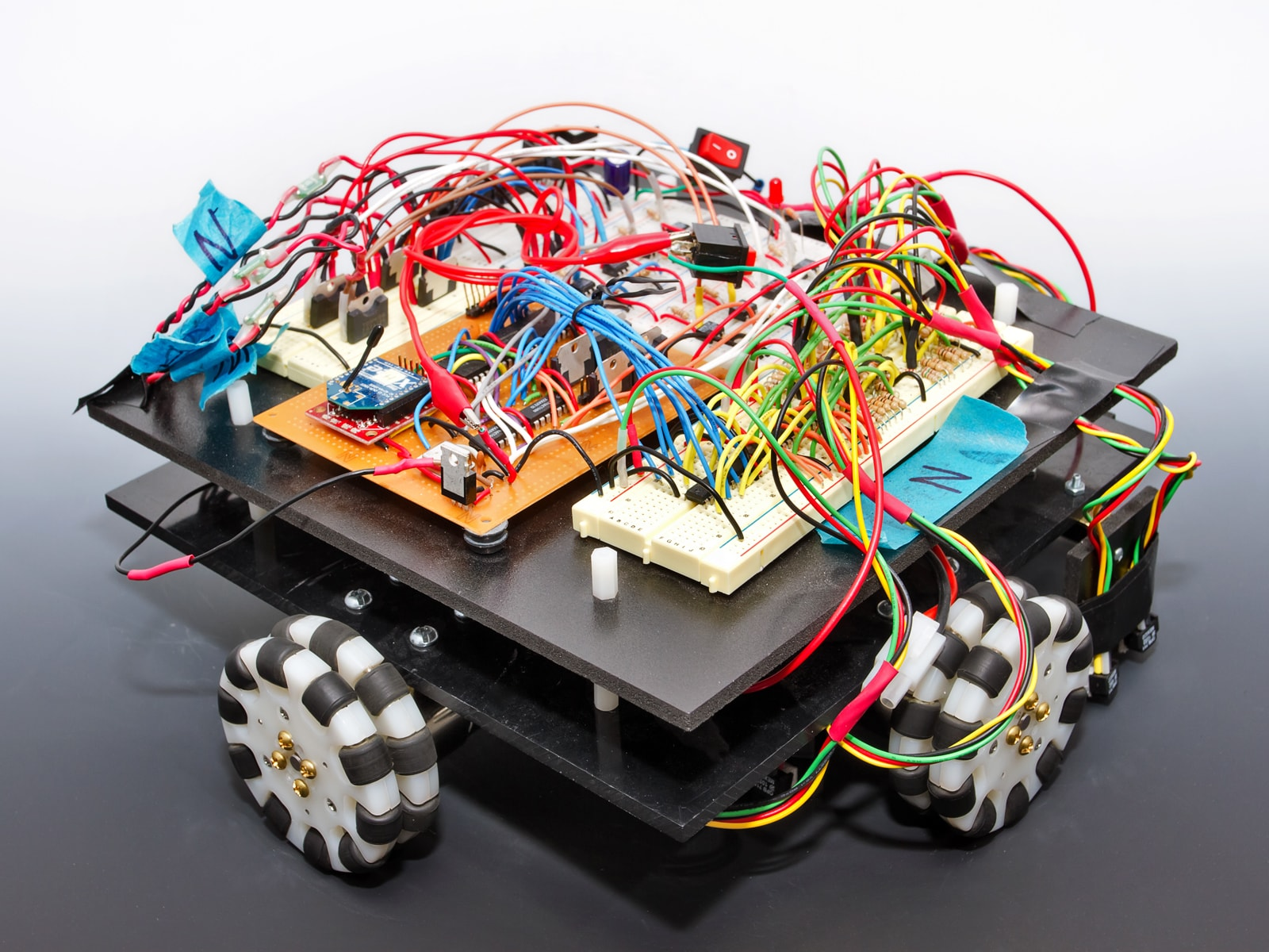 A square robot with exposed circuitry and black and white wheels.