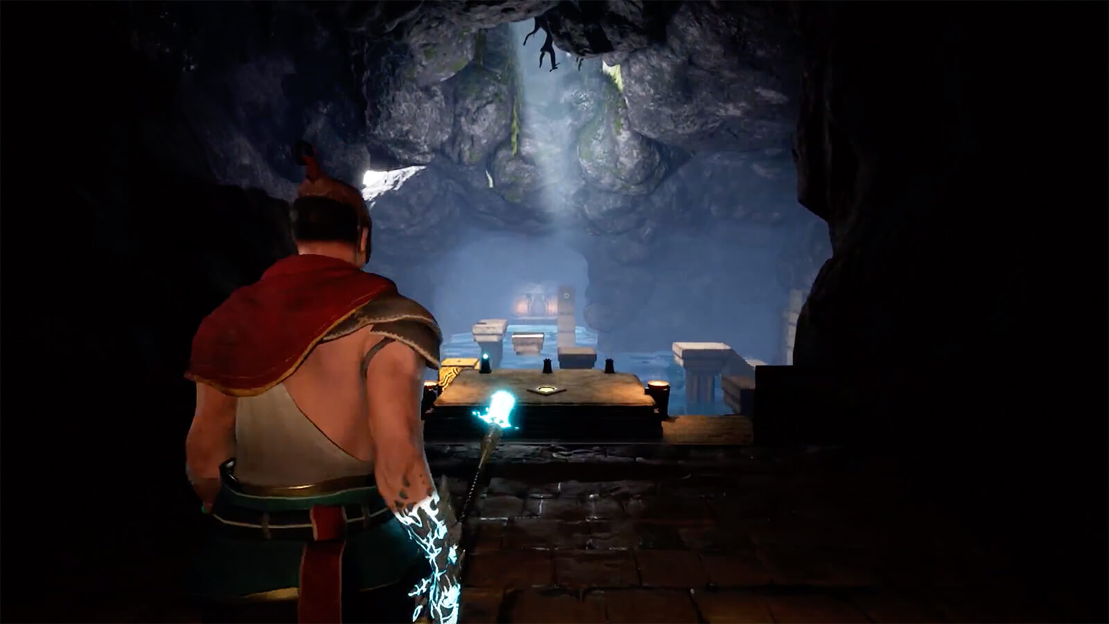 A man faces an opening in a cavern, holding a glowing spear.