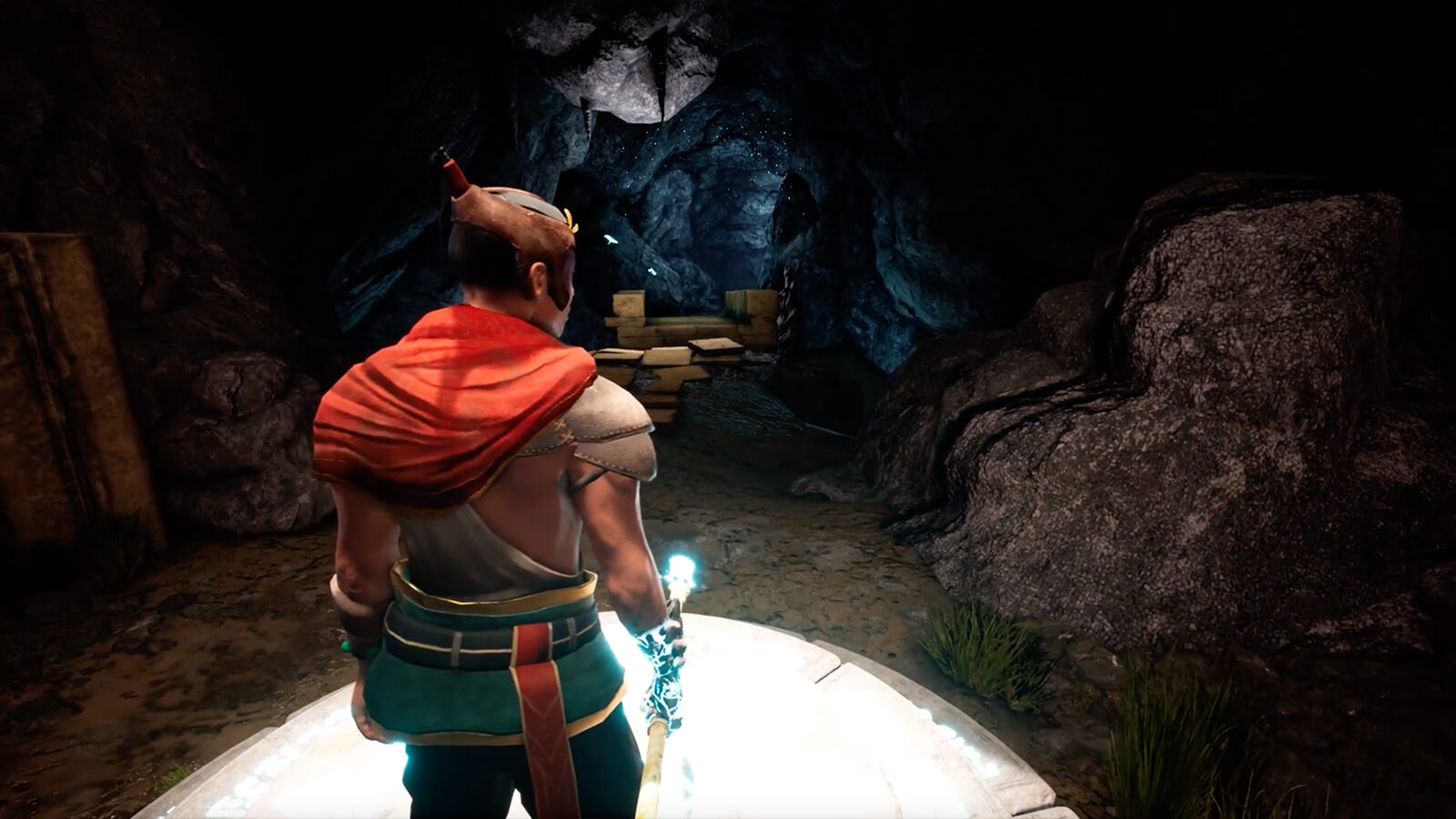 A man in a cavern holding a glowing spear.