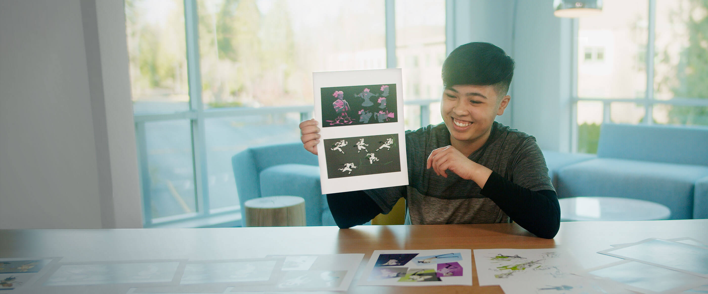 Student A.D. Taeza, seated in a brightly lit room, showcases her work smiling.