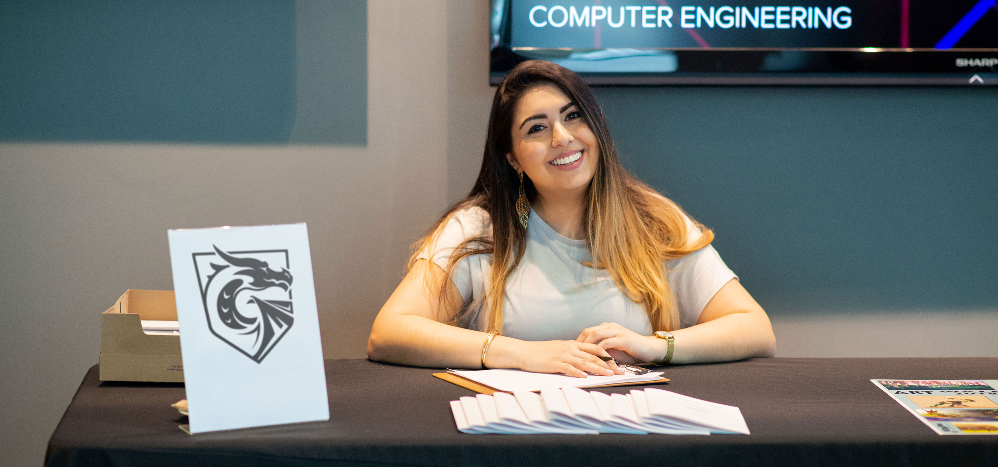 A smiling woman sits at a table welcoming people to an event on DigiPen's campus.