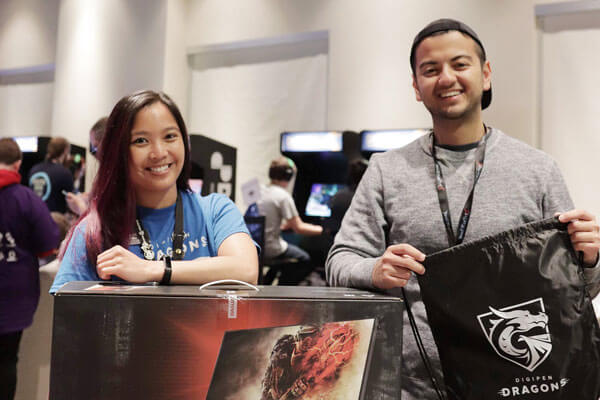 Two employees at a convention hall pose with a black DigiPen Dragons drawstring backpack and boxed computer monitor.