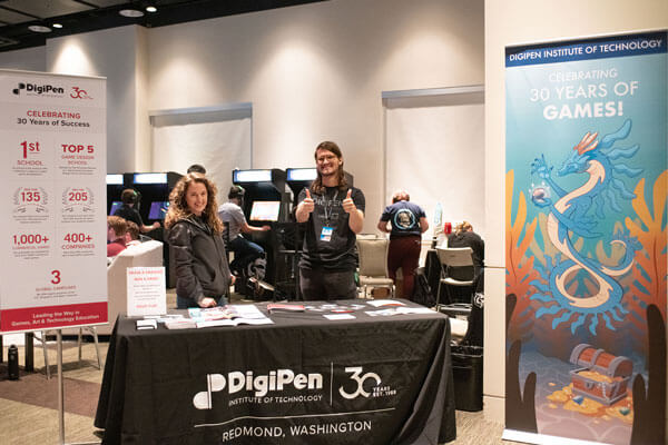 Two employees stand behind a DigiPen convention table in front of a row of arcade cabinets.
