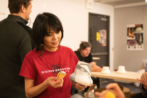 In an art studio, a woman in a red DigiPen Dragons t-shirt decorates a piece of kiln-fired pottery.