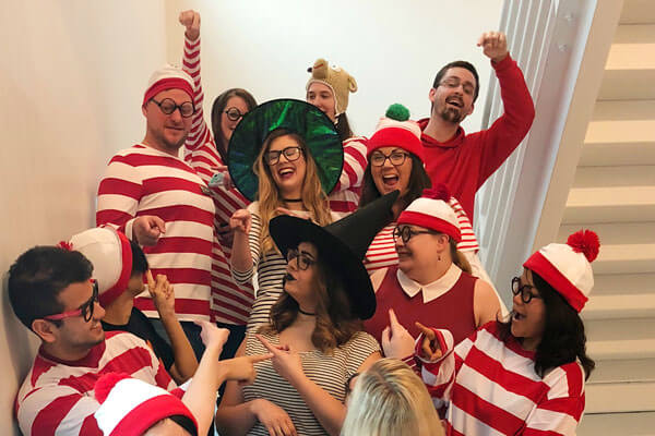 A handful of DigiPen staff wearing Waldo costumes pose in a white stariwell.