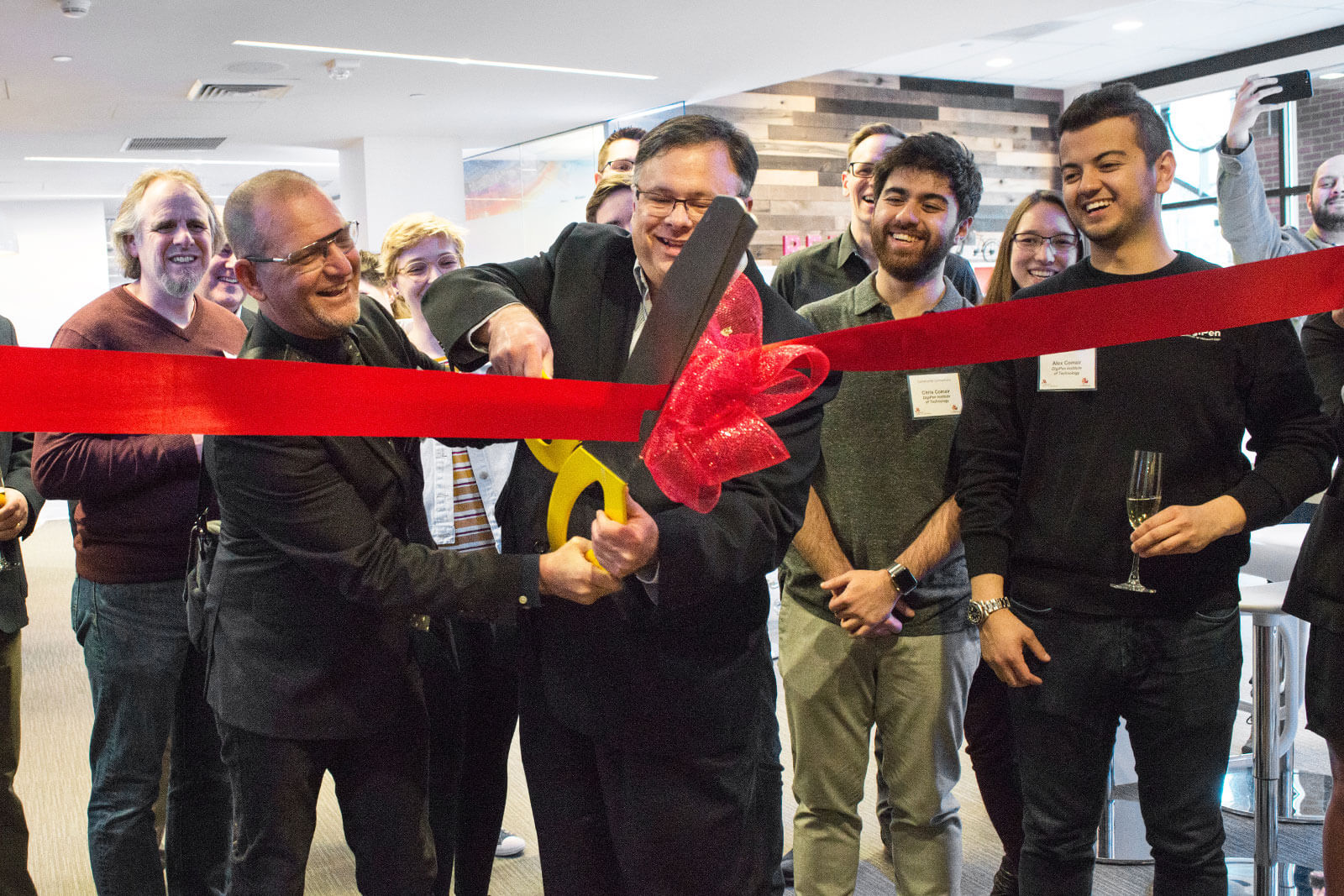 Two men cut through a large red ribbon with oversized scissors while a group of smiling people stand behind them.