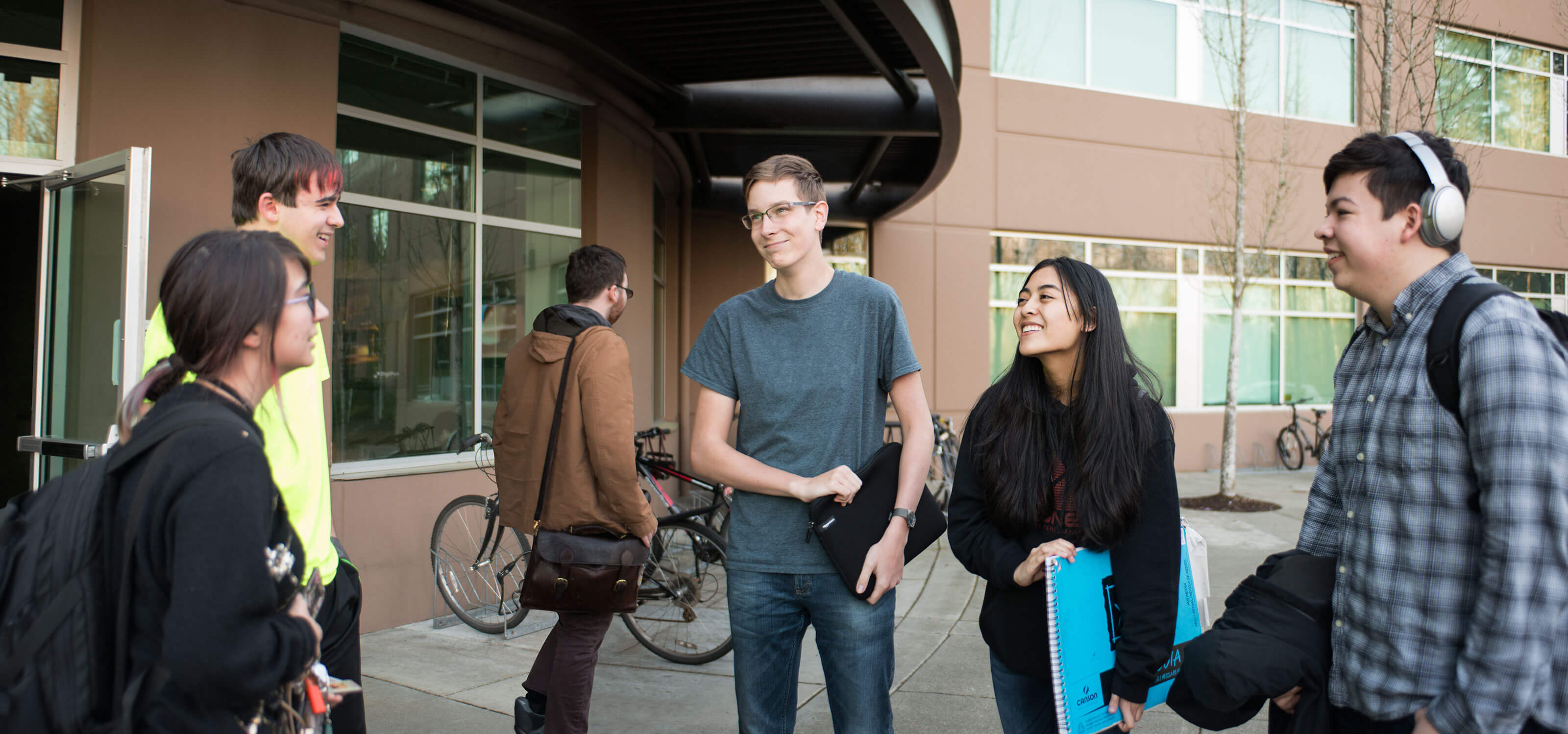 A group of students stand smiling at each other in front of the first-floor lobby of a brown building.