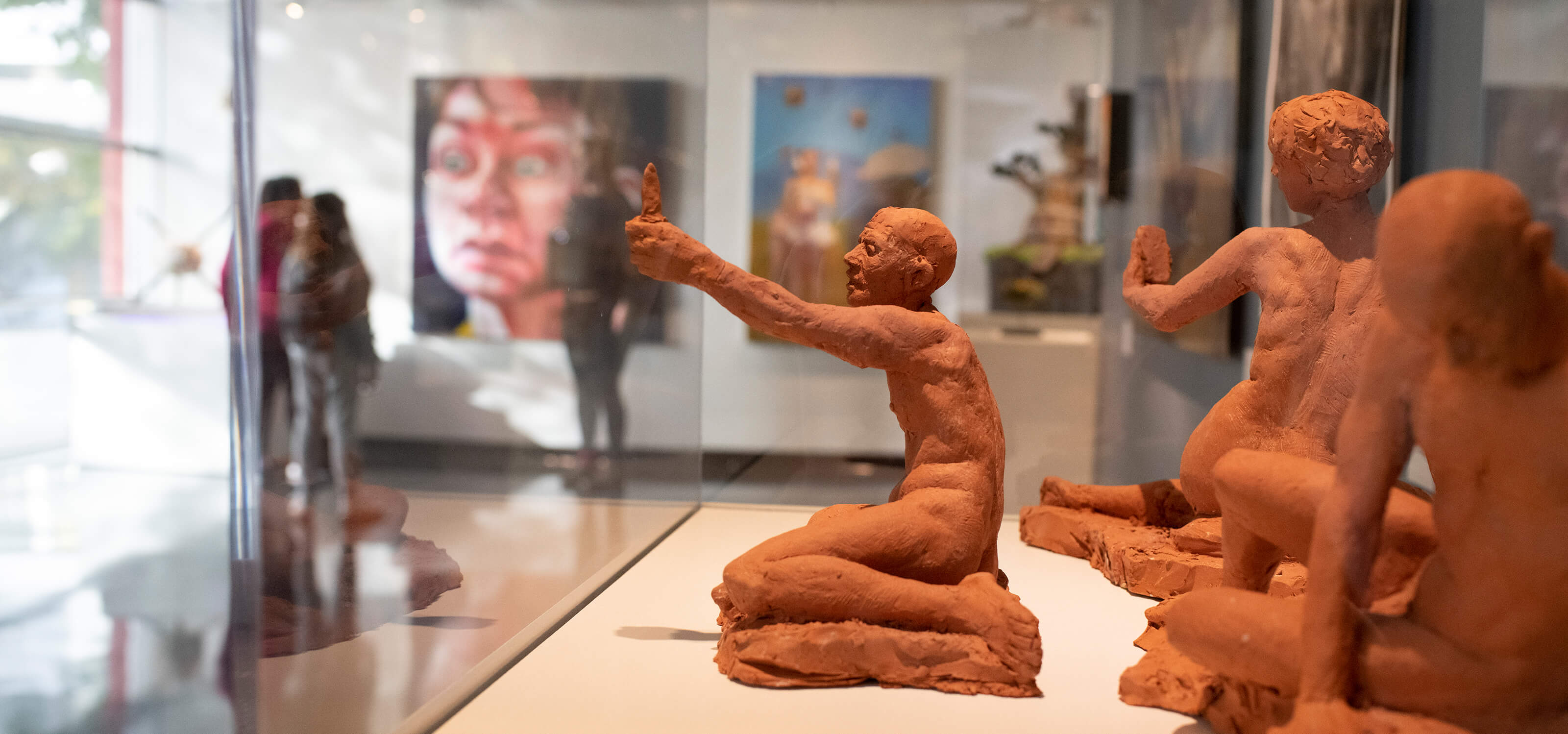 Three terracotta figure sculptures by Alecia Rossano on display at the Bellevue Art Museum.