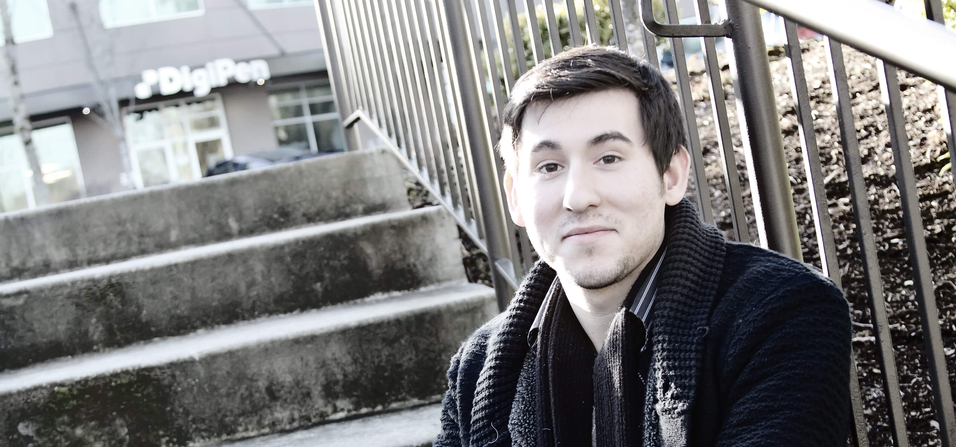 DigiPen student Andrew Alvarez posing on stairs outside the DigiPen building