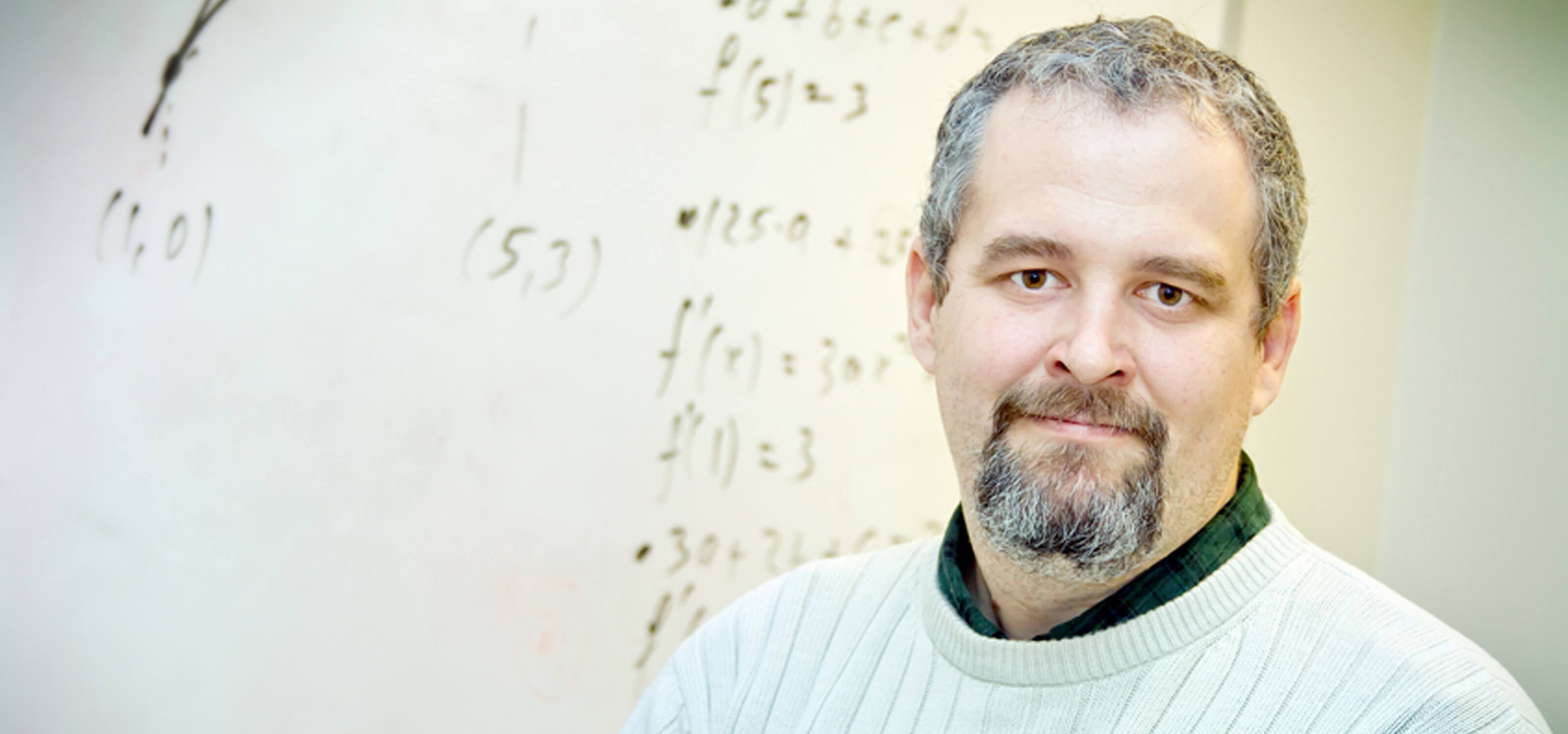 DigiPen mathematics professor Barnabas Bede smiling in front of a whiteboard decorated with mathematical formulas