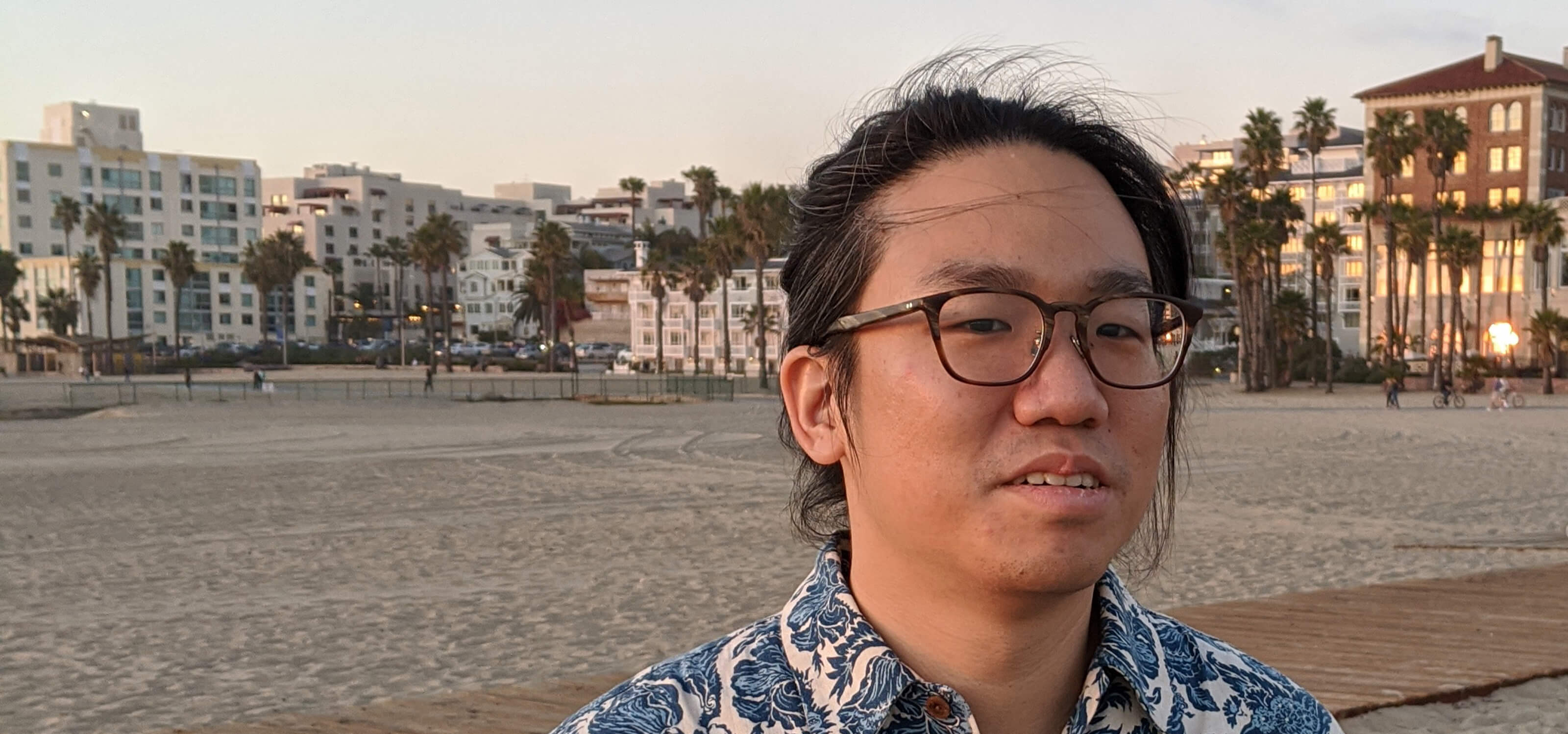 DigiPen graduate Chia-Hao Ching poses on a beach lined with palm trees.