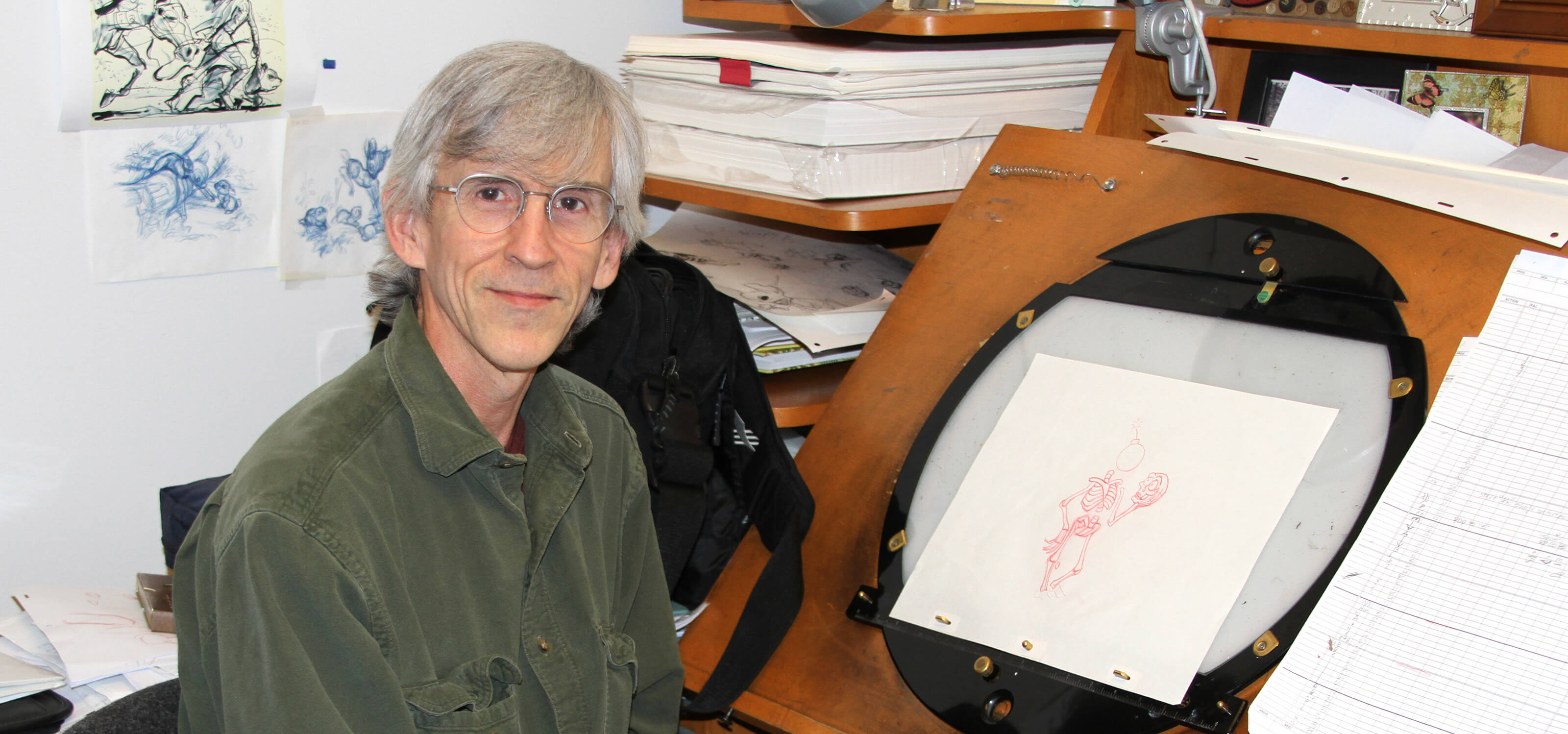 DigiPen animation professor Dan Daly sits at his desk with an original rough in-between drawing from the Aladdin game.