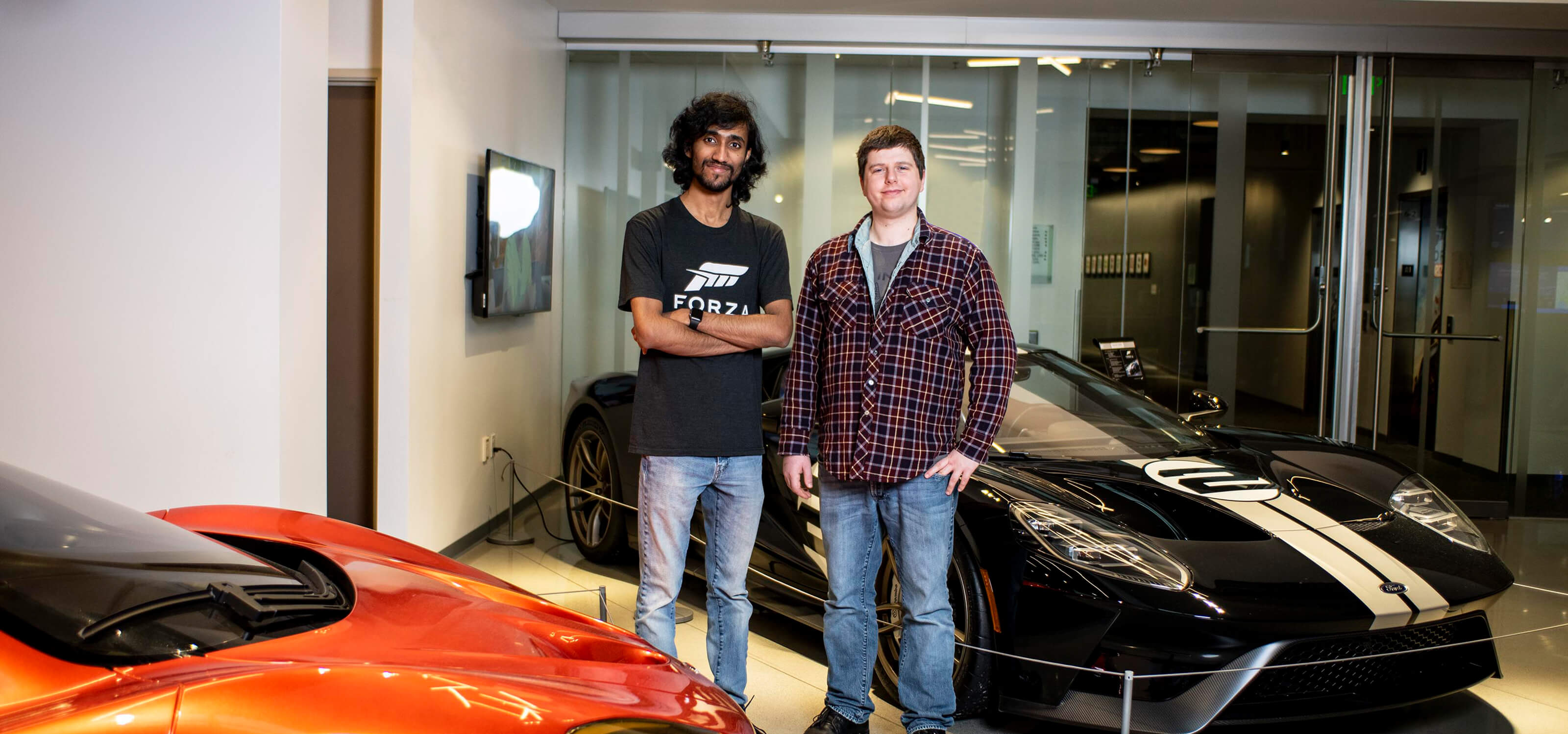 Michael Pitaniello and Deepak Chennakkadan stand next to luxury cars in the Turn 10 Studios lobby.