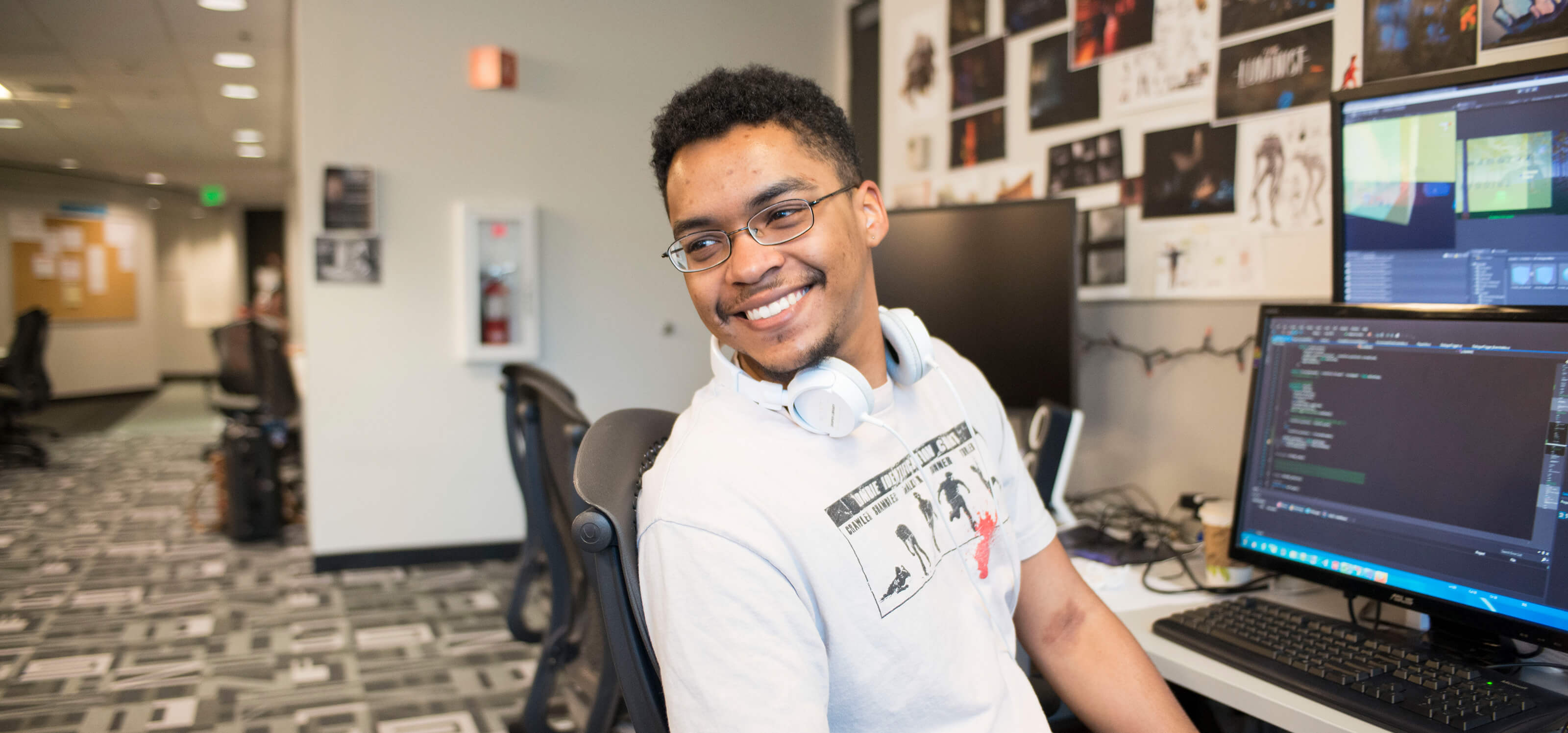 A DigiPen student smiling as he leans away from a computer screen