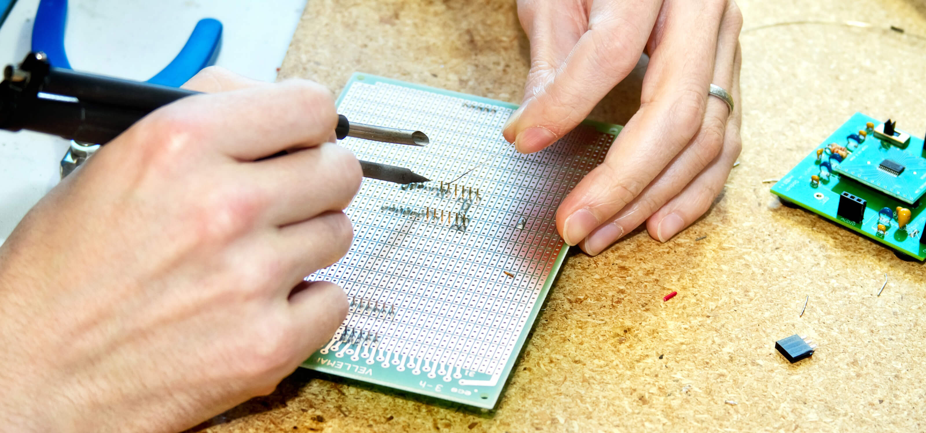 Close-up of a DigiPen student doing detailed work on a small circuit board