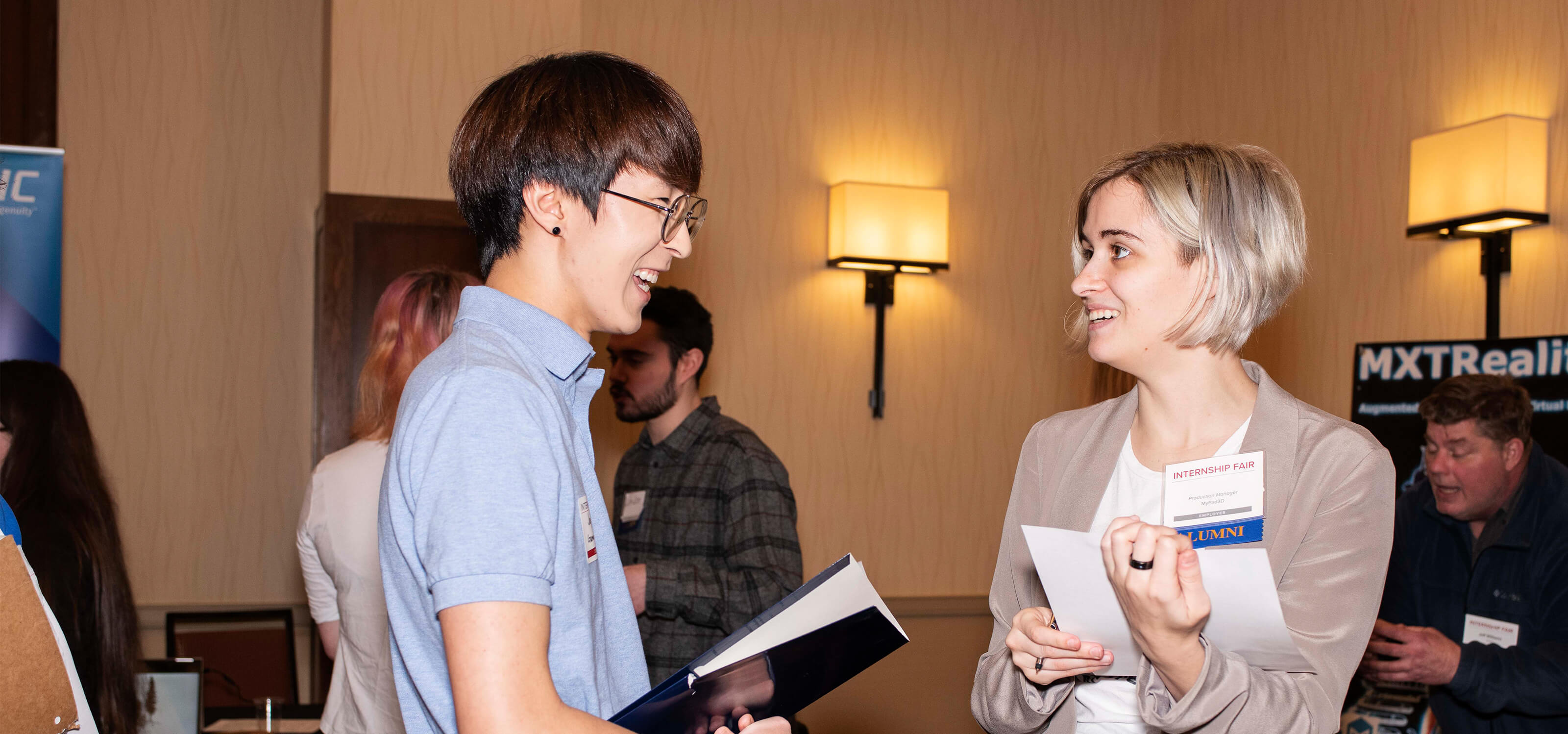 A company representative with an alumni tag chats with a current student at the 2019 Internship Fair.