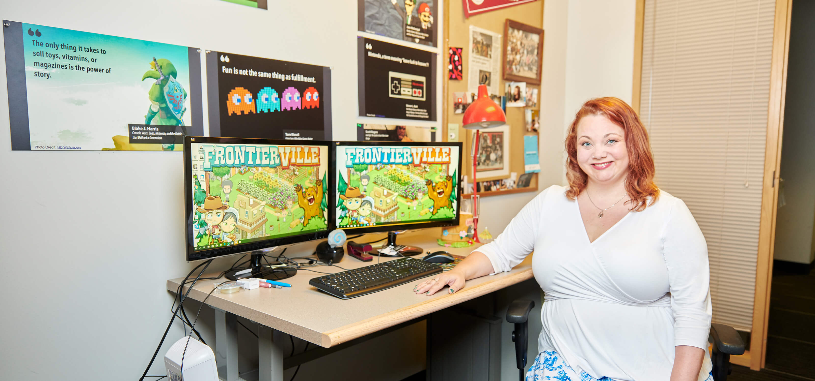 DigiPen game design lecturer Angie Hoffman poses in her office with her game title FrontierVille on display.