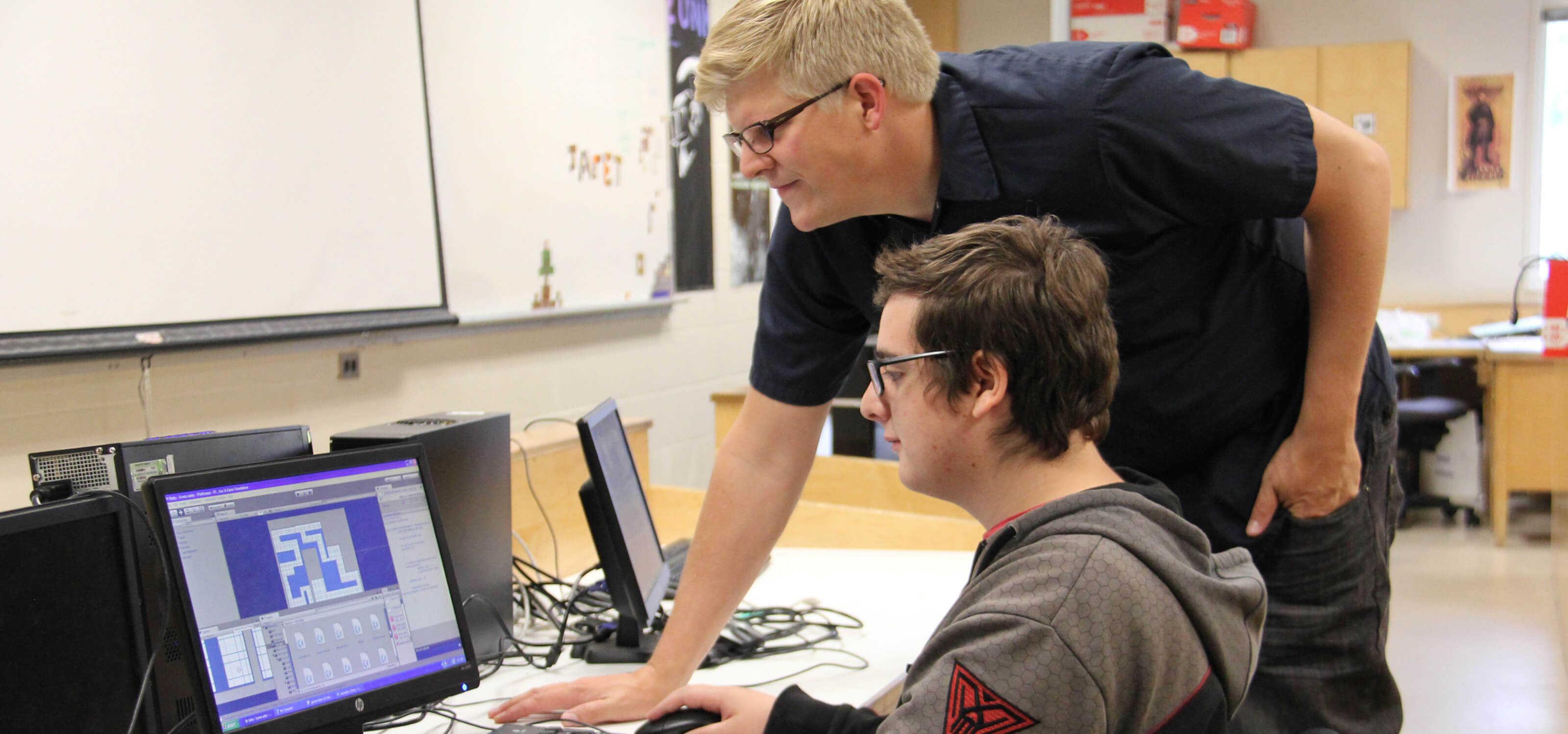 Student and teacher looking at a computer monitor in a Kamloops, British Columbia classroom