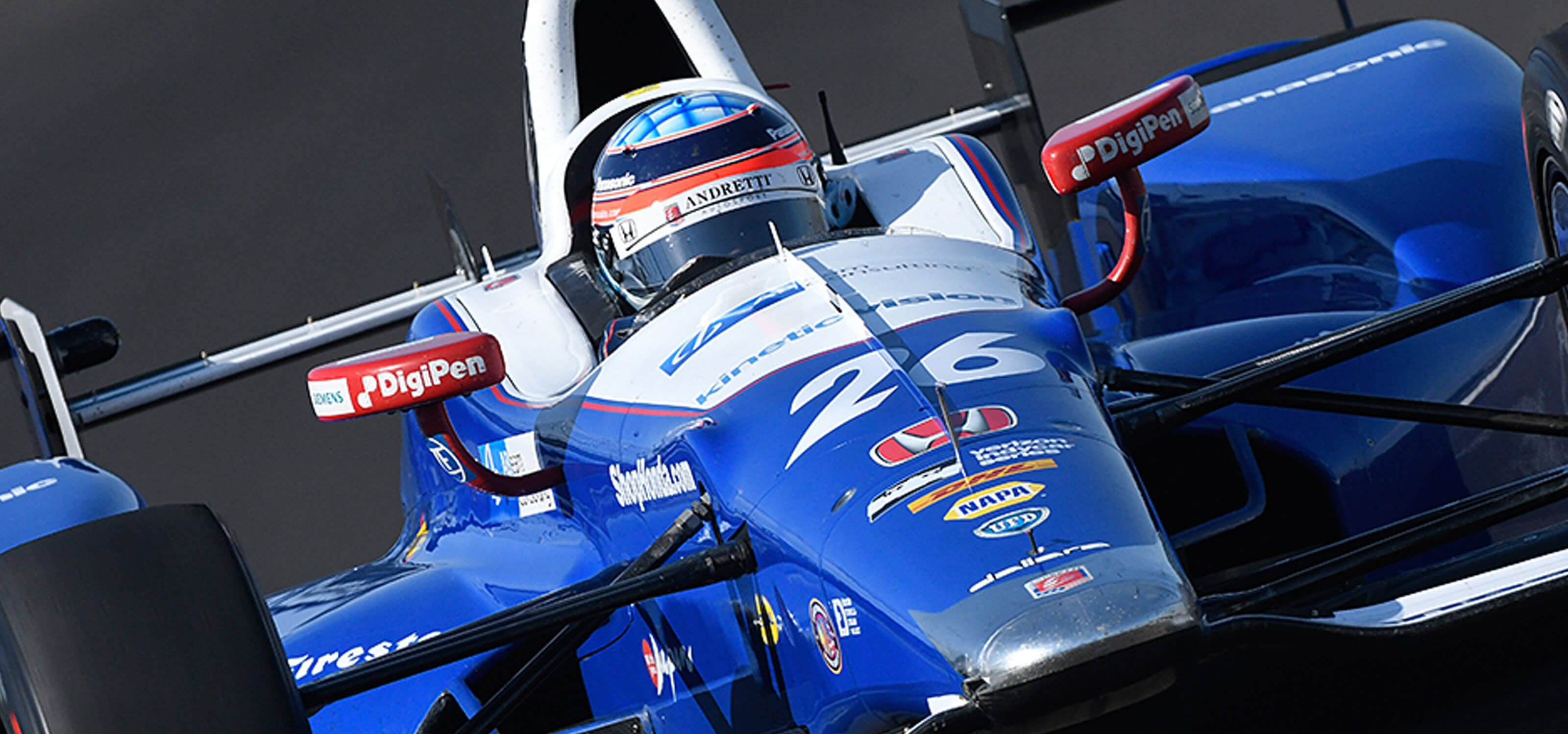 Takumo Sato driving an Indy car featuring the DigiPen logo
