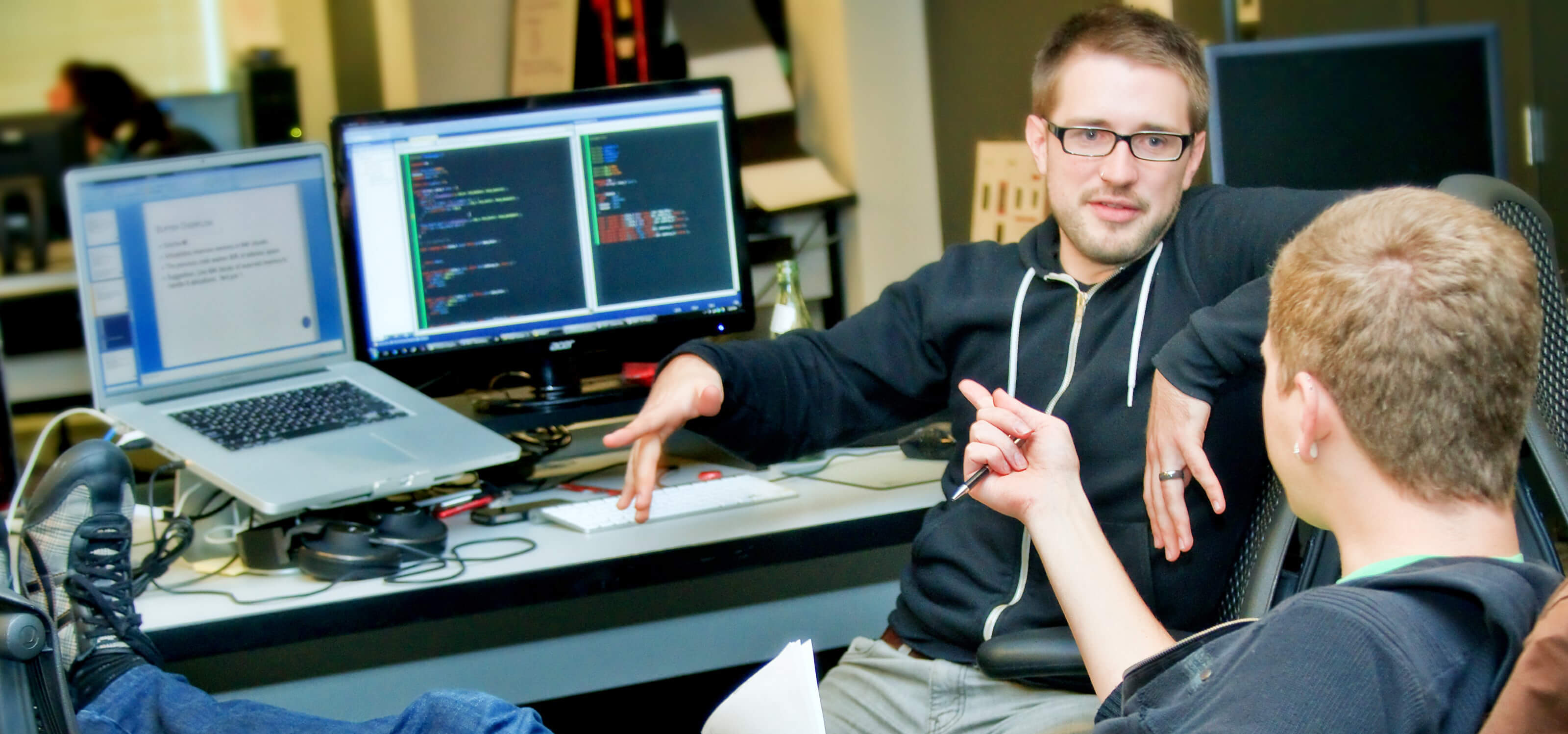 Two students chatting in their team space on the DigiPen campus